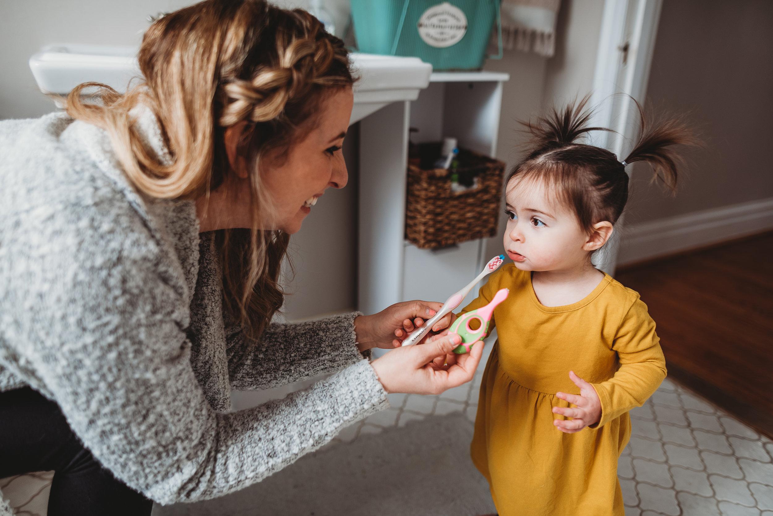 mom and toddler brushing teeth