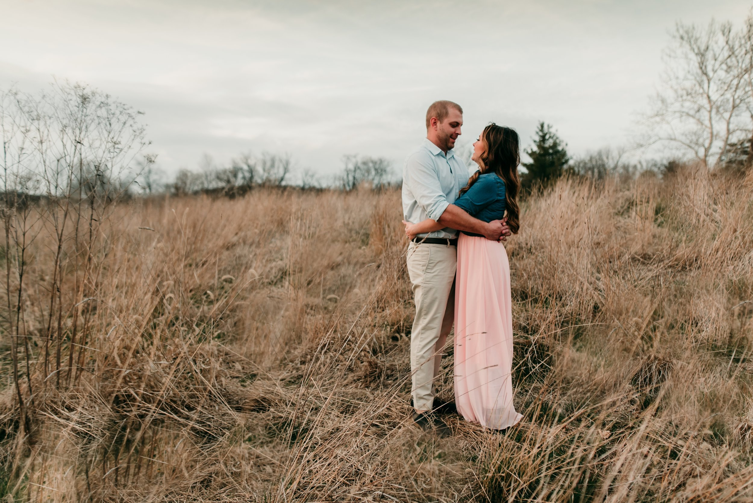 couple holding each other in field
