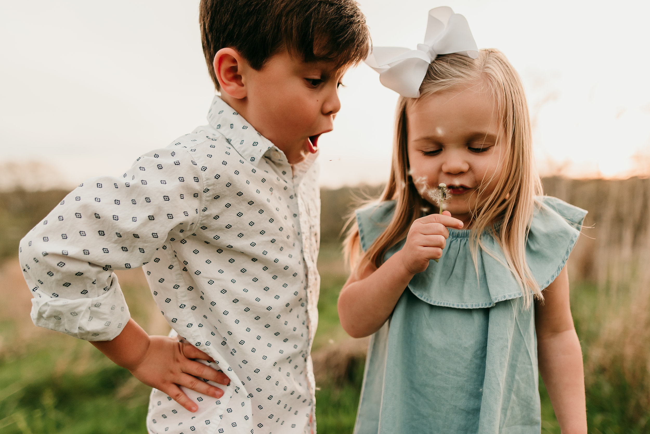 brother and sister trying to blow flower