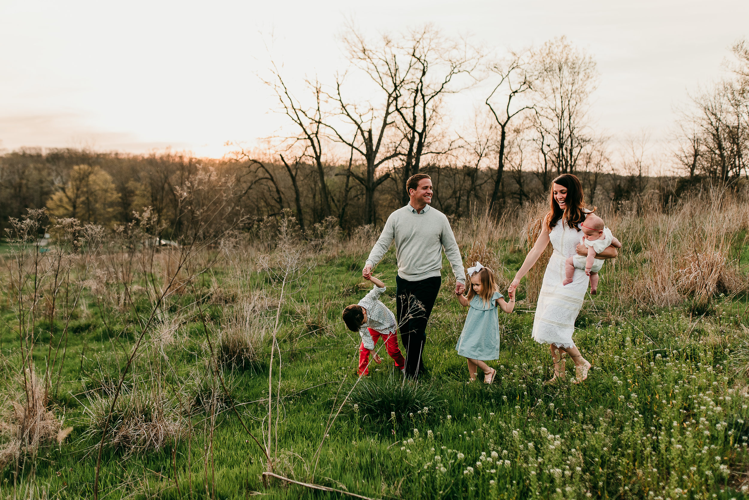 family walking down hill in a field