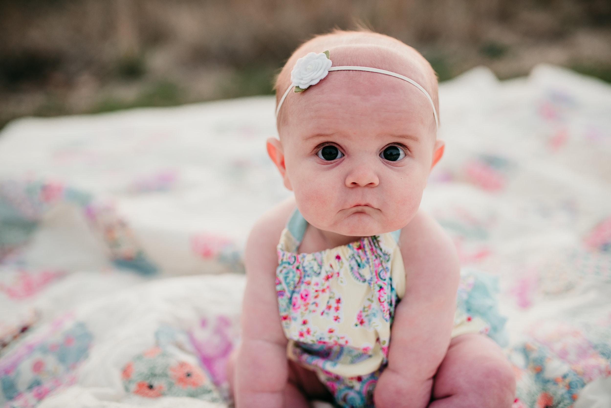 baby girl sitting on blanket