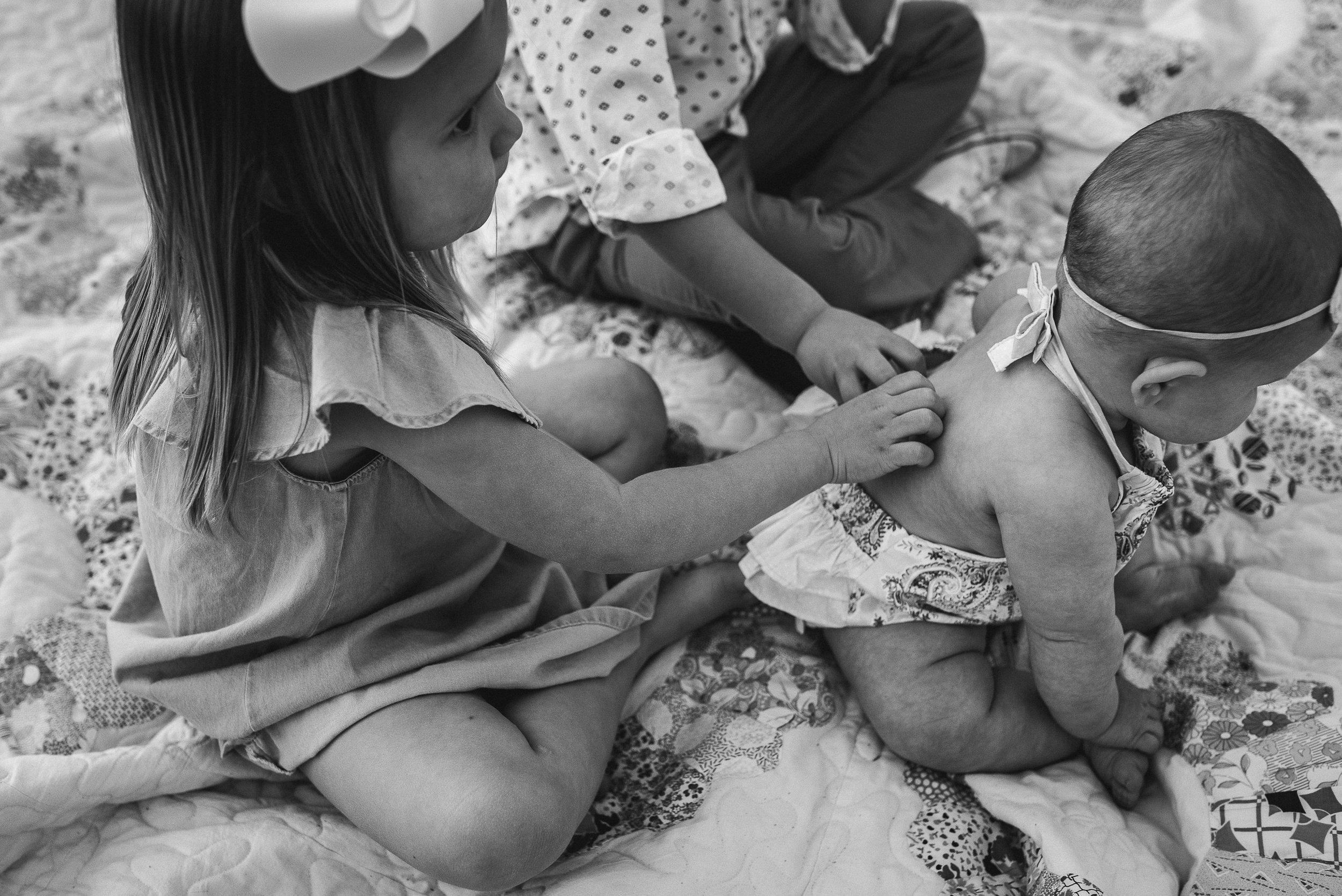 siblings scratching baby sister's back