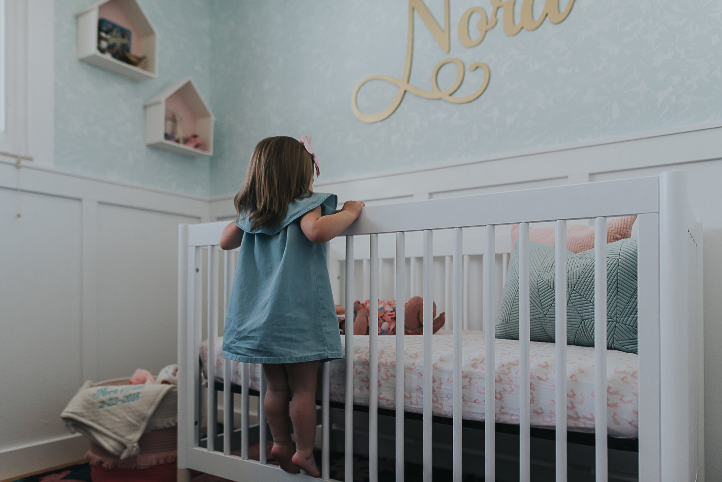 sister looking through her crib