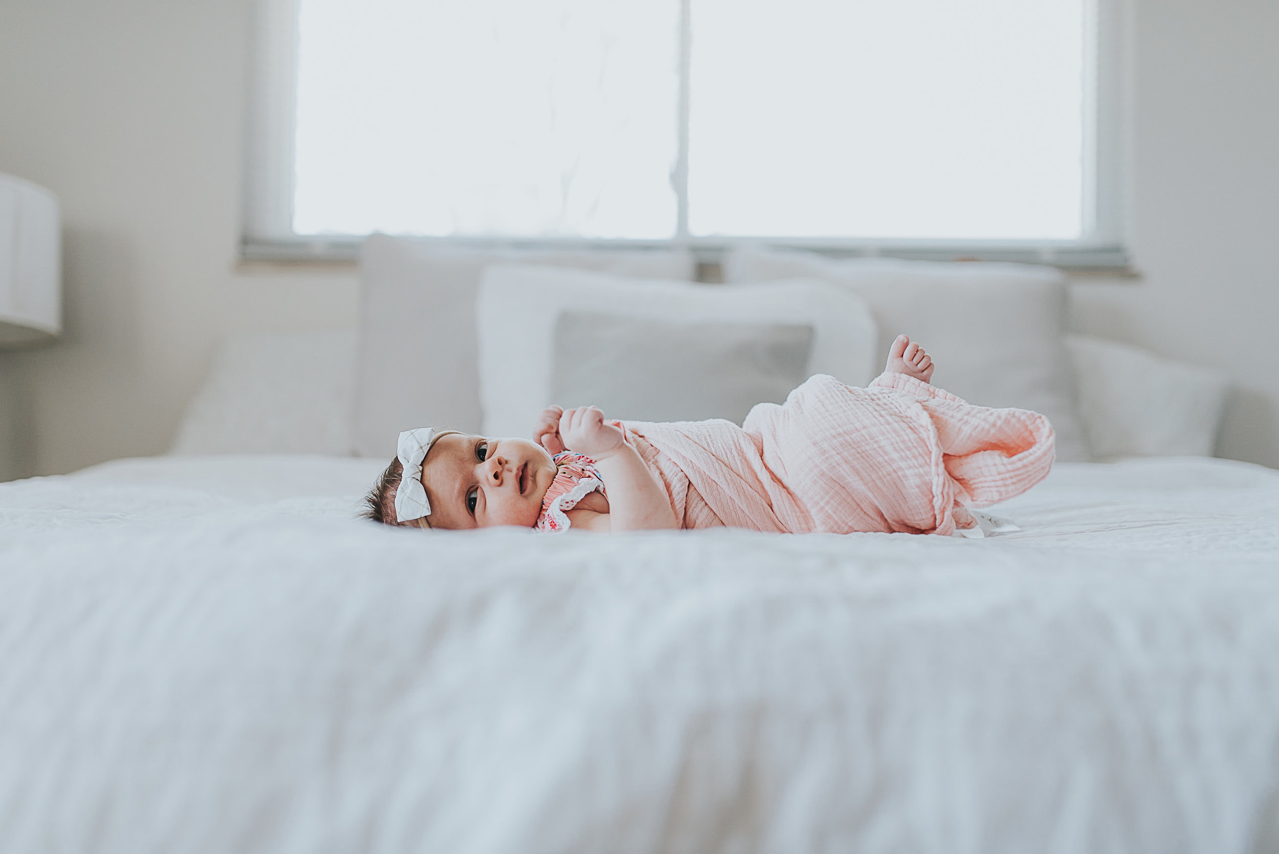baby laying on bed St. Louis Photographer
