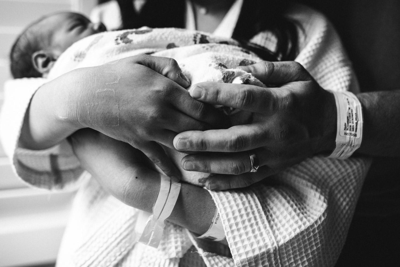 parents hands holding newborn