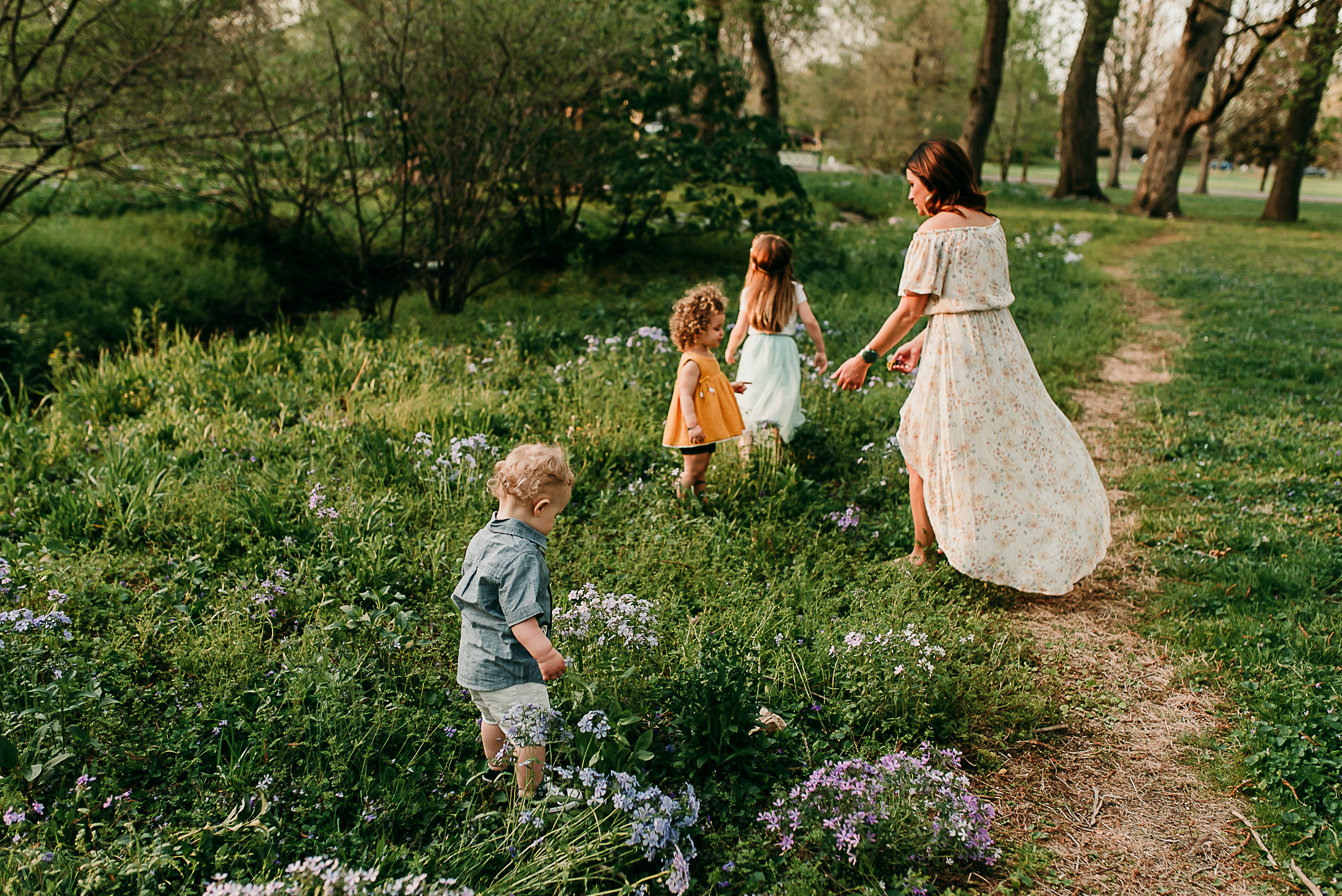 mom walking with children in a field