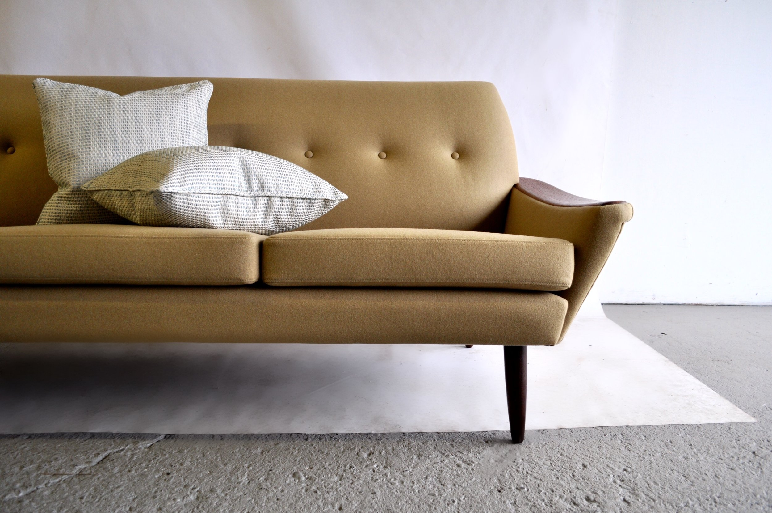 Mid Century Modern sofa, with topstitch detail and button tufting.