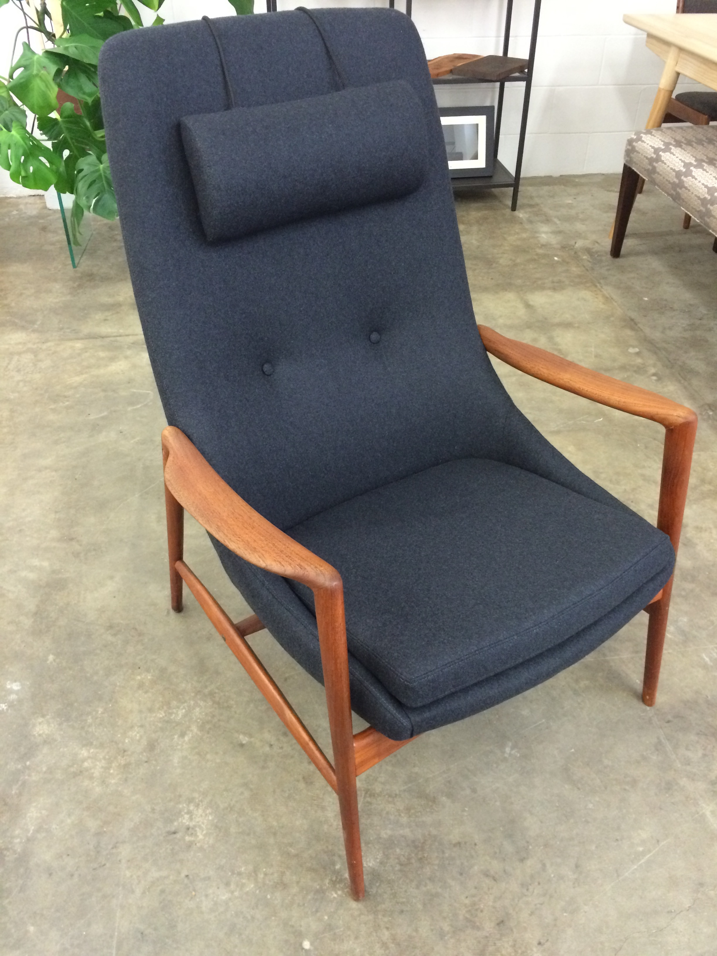 Mid Century Modern teak arm chair, with button tufting and a weighted headrest.