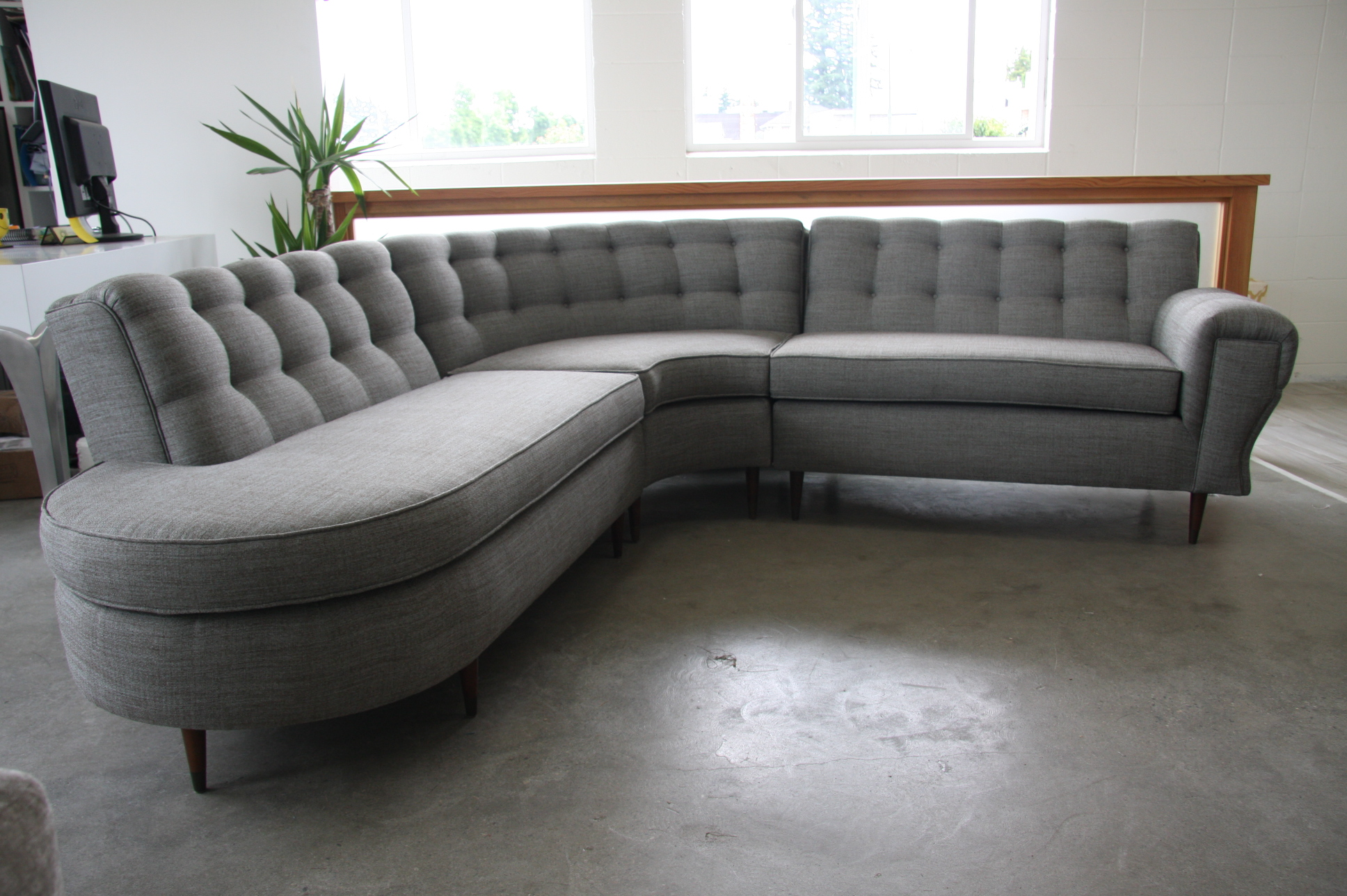 Vintage curve sectional with button tufting and piping trim.
