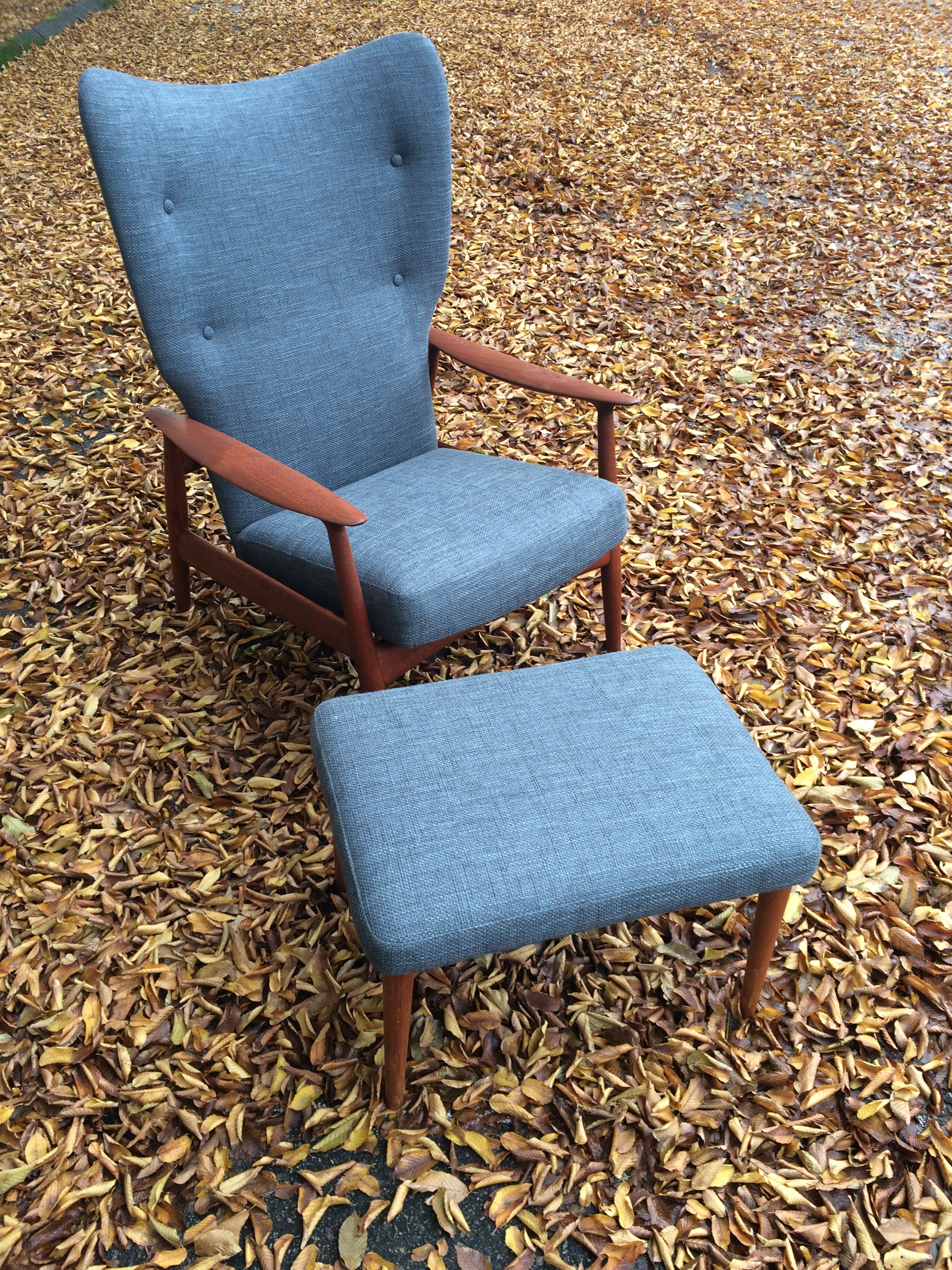 Mid Century Modern armchair and ottoman, with button tufting on inside back and topstitched borders.