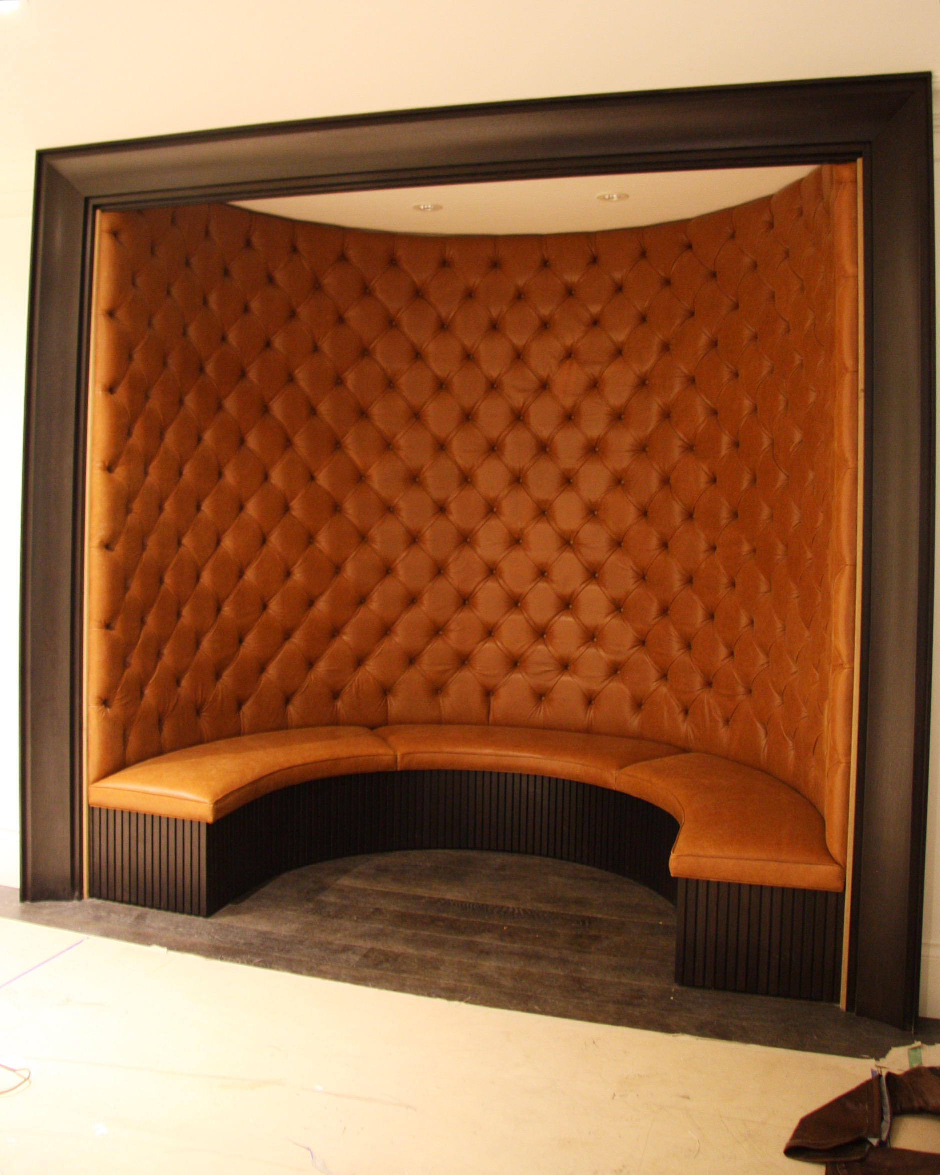 Upholstered curve banquette, featuring diamond tufting detail and piping trim on seats.