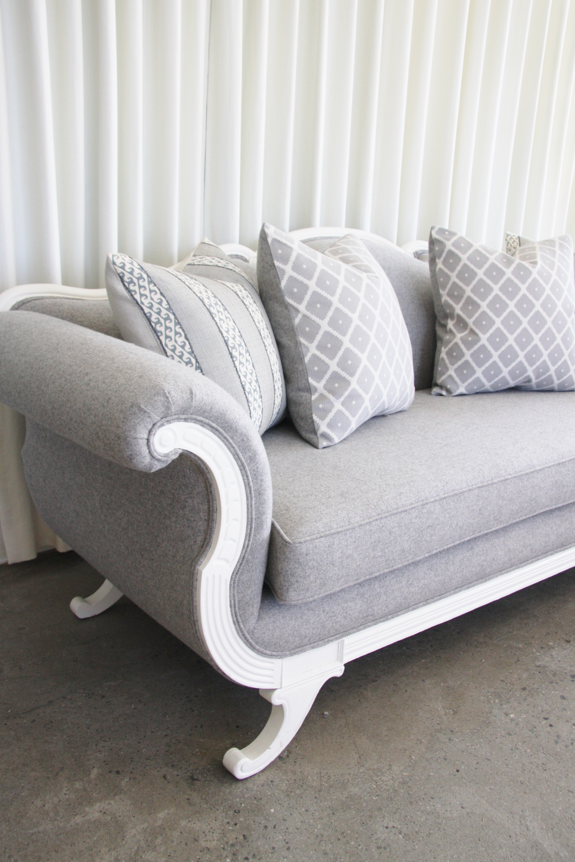 Fresh toss pillows sit atop a restored antique sofa, upholstered in grey wool featuring double piping trim. Lacquer painted wood.