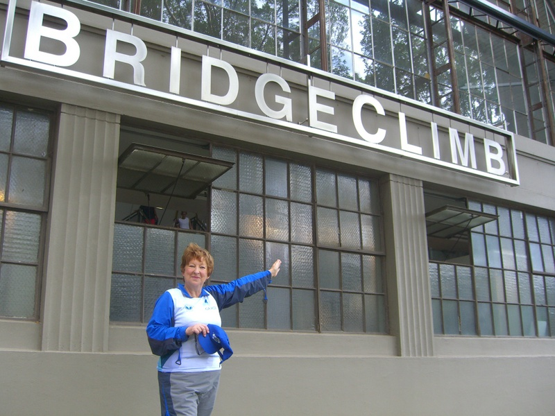 Jill in front of the Bridge Climb sign at Sydney Harbour Bridge fundraising on behalf of GRACE