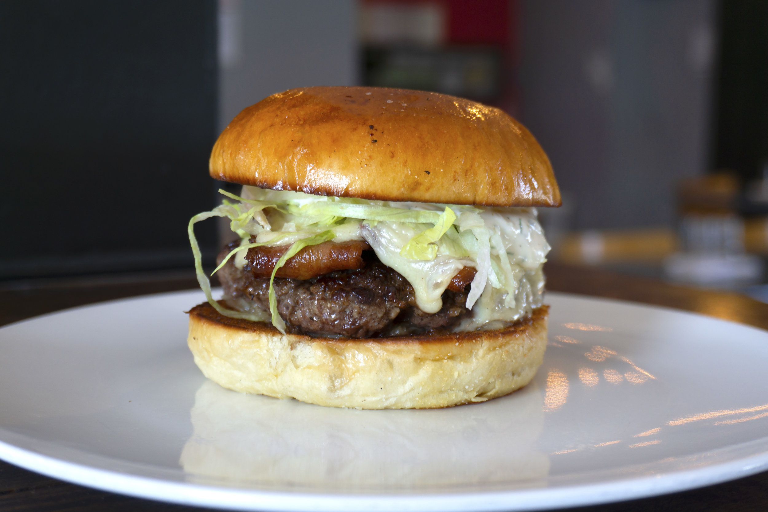 brioche bun, hand pressed angus beef patty, onion jam, cucumber dill mayo, bacon, swiss, shredded lettuce