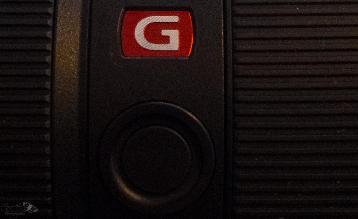 """Le bouton de verrouillage de la mise au point, sous le sigle """"G"""" rouge-orangé représentatif de la gamme."""