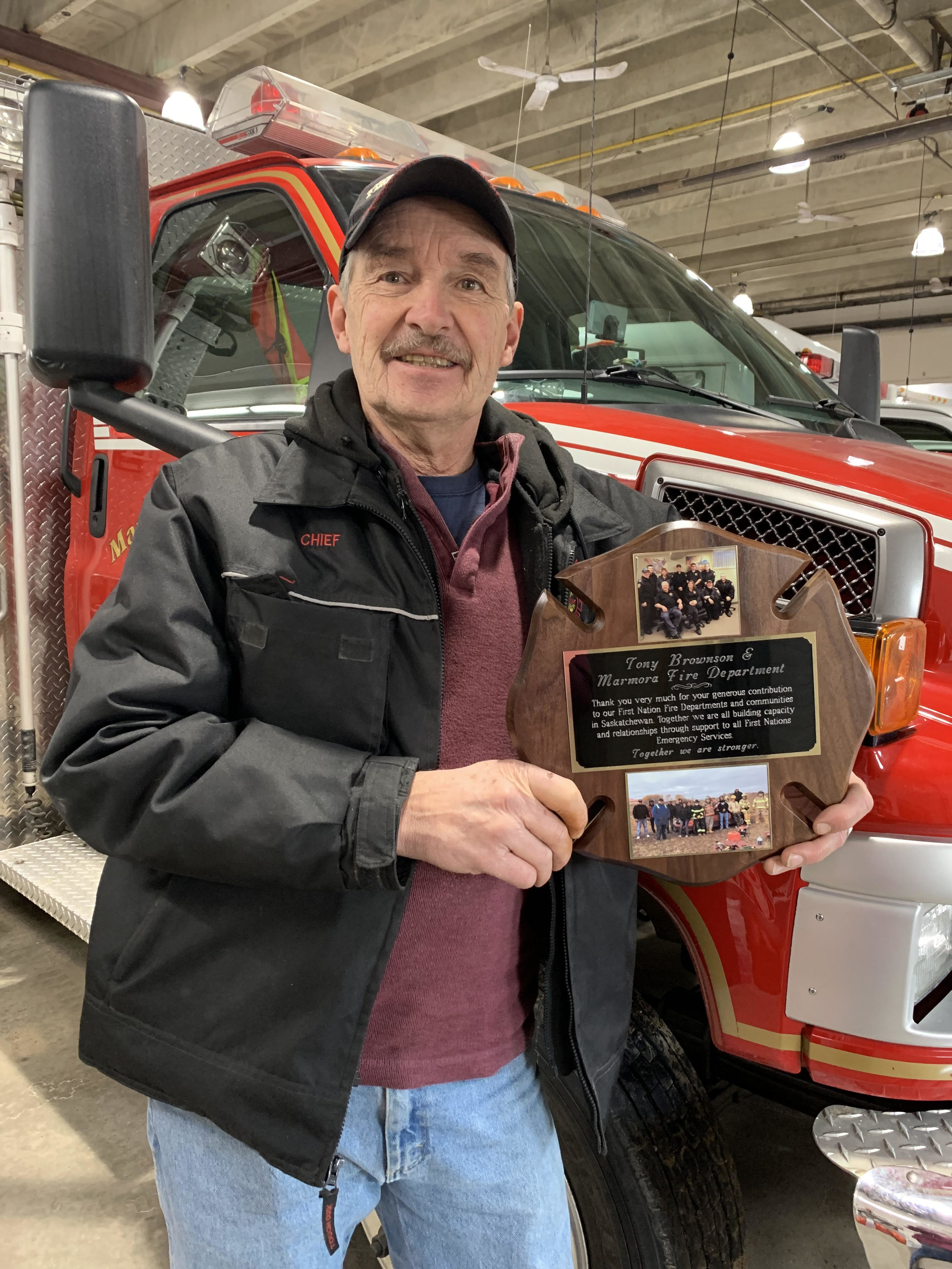 Fire Chief Tony Brownson shows the plaque sent to him by First Nations Emergency Services for his efforts to provide First Nation Fire Departments with good used equipment.