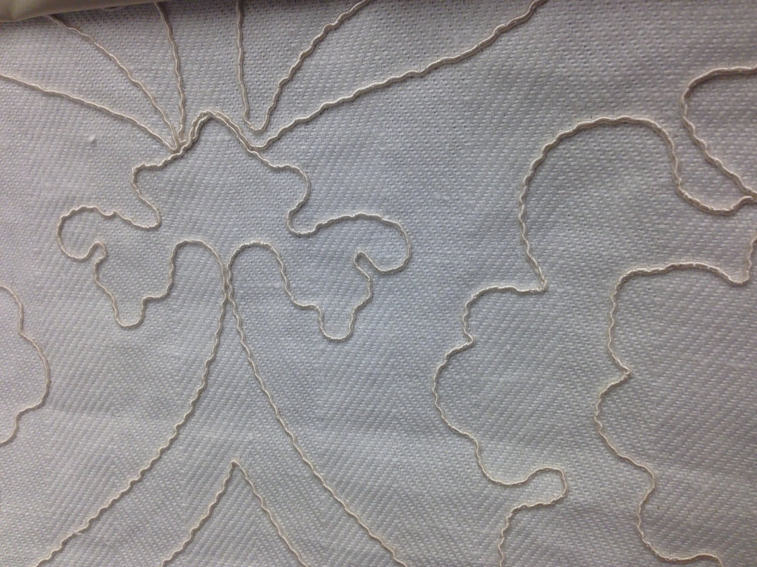 embroidered damask pattern on herringbone weave