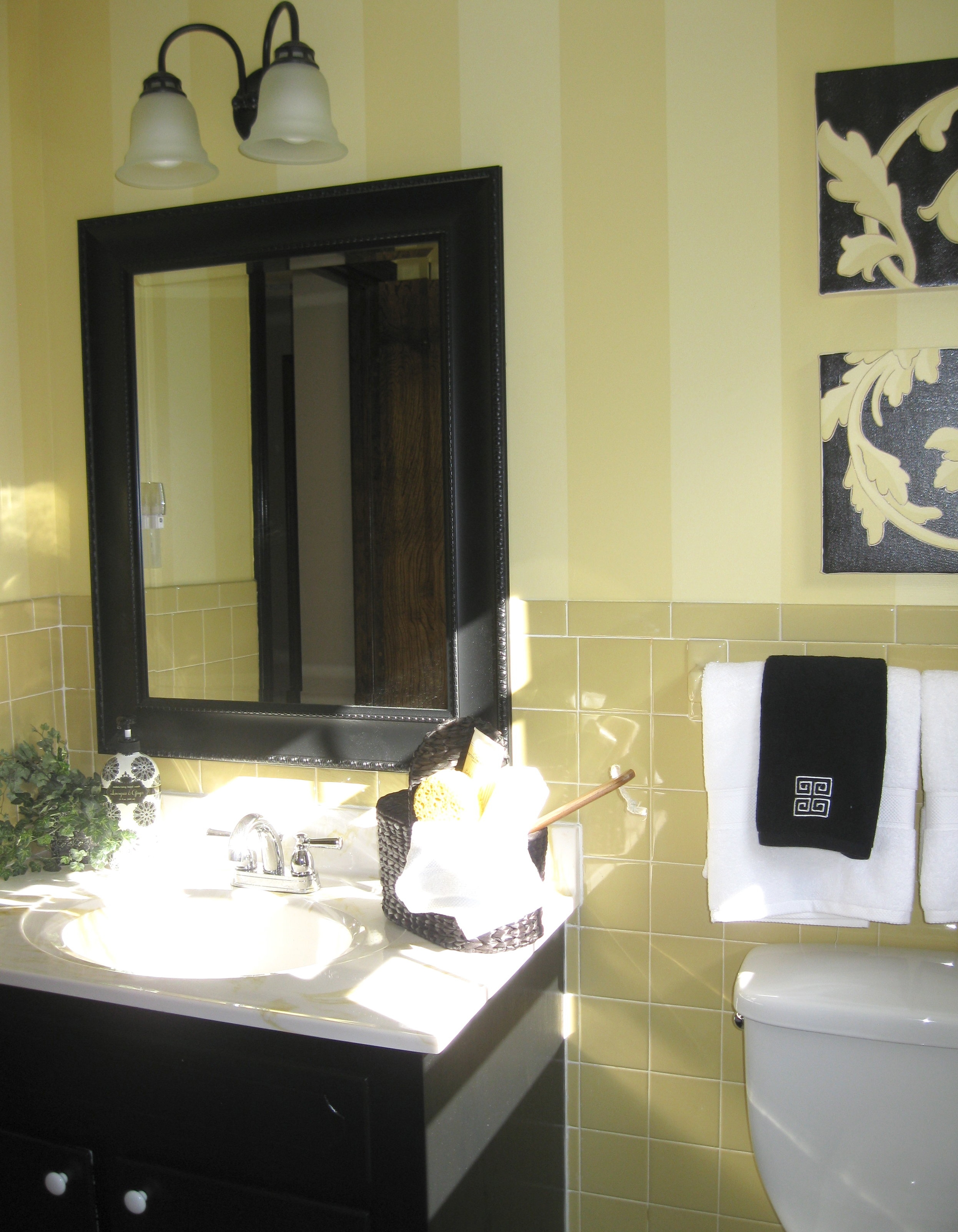 - This dated harvest gold bathroom  was salvaged by painting the cabinetry and millwork in a glossy black and the walls in a tone on tone wide stripe selected to blend with the existing tiles for a budget conscious makeover.