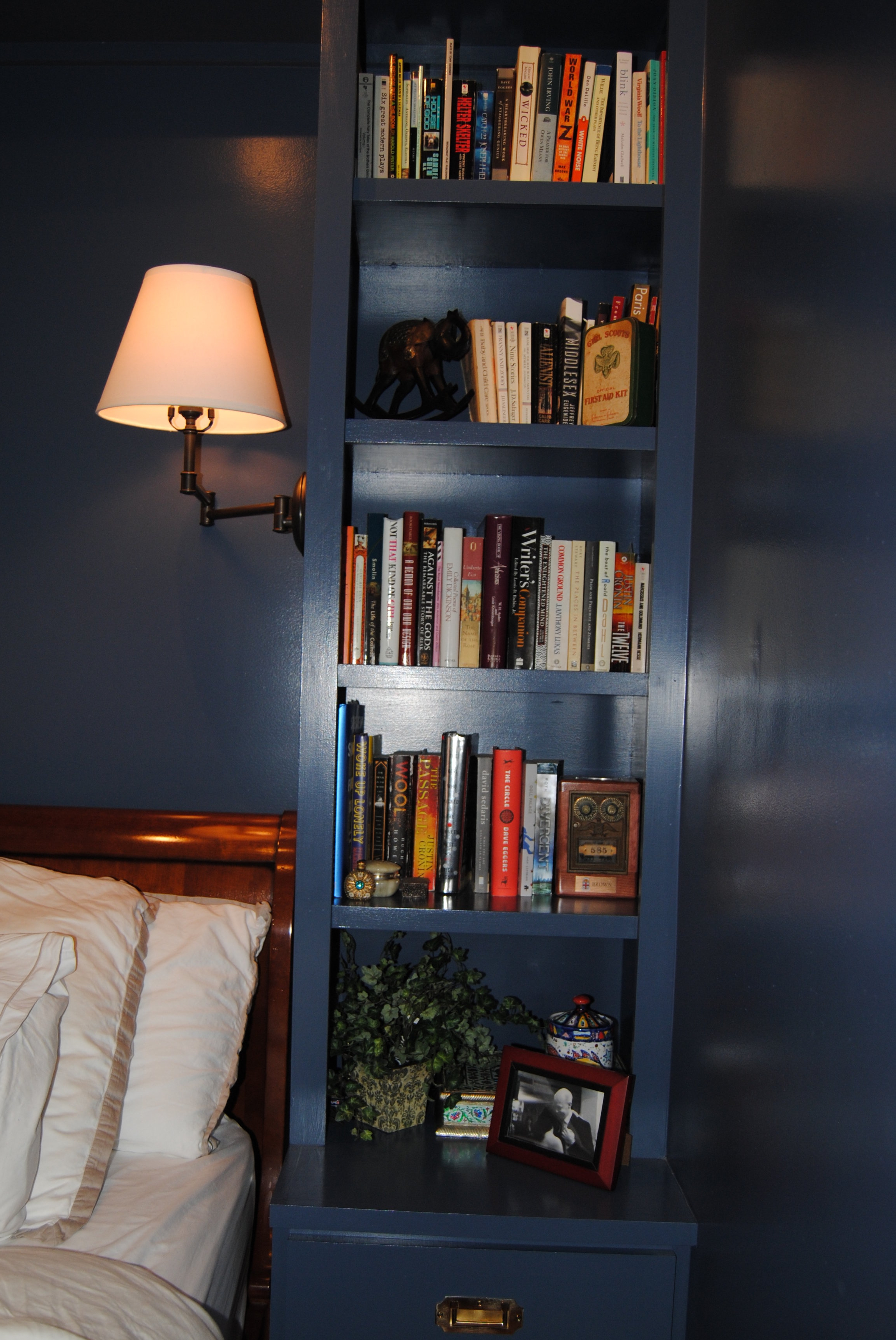 - High gloss marine blue paint on both walls and built-ins give this master bedroom a cozy library feel