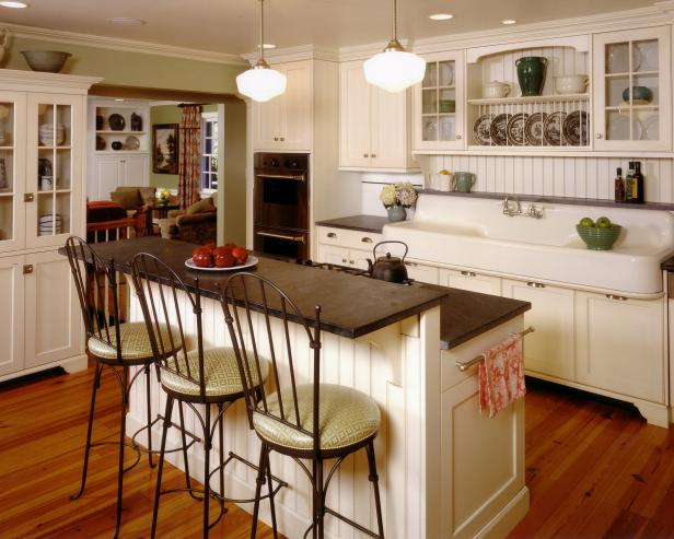 Bar height stools at the bi-level counter in this country kitchen via   HGTV.com