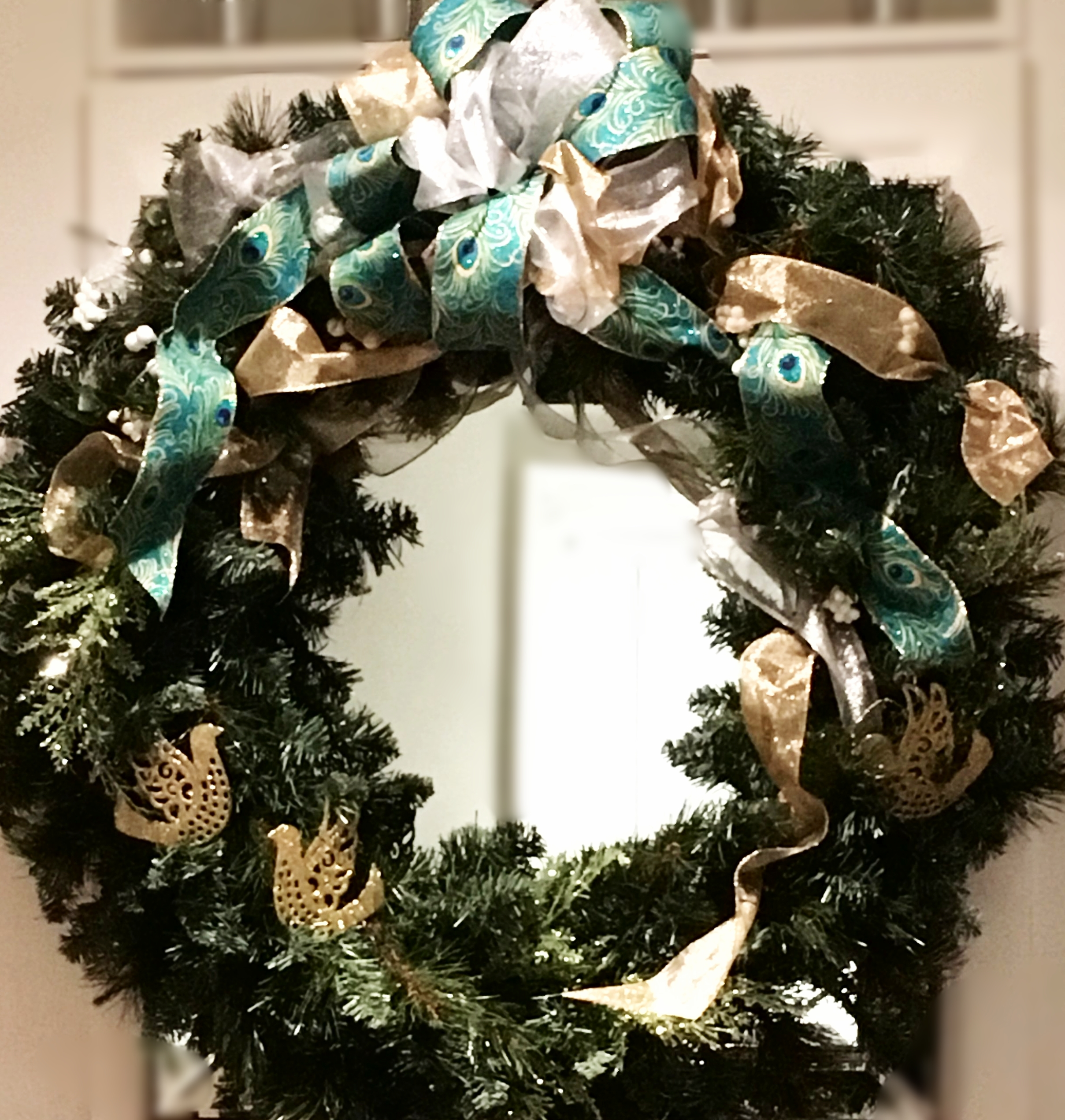 A large wreath over a fireplace is embellished with peacock ribbon mixed with gold and silver ribbon, glittered cedar greens, and gold bird ornaments