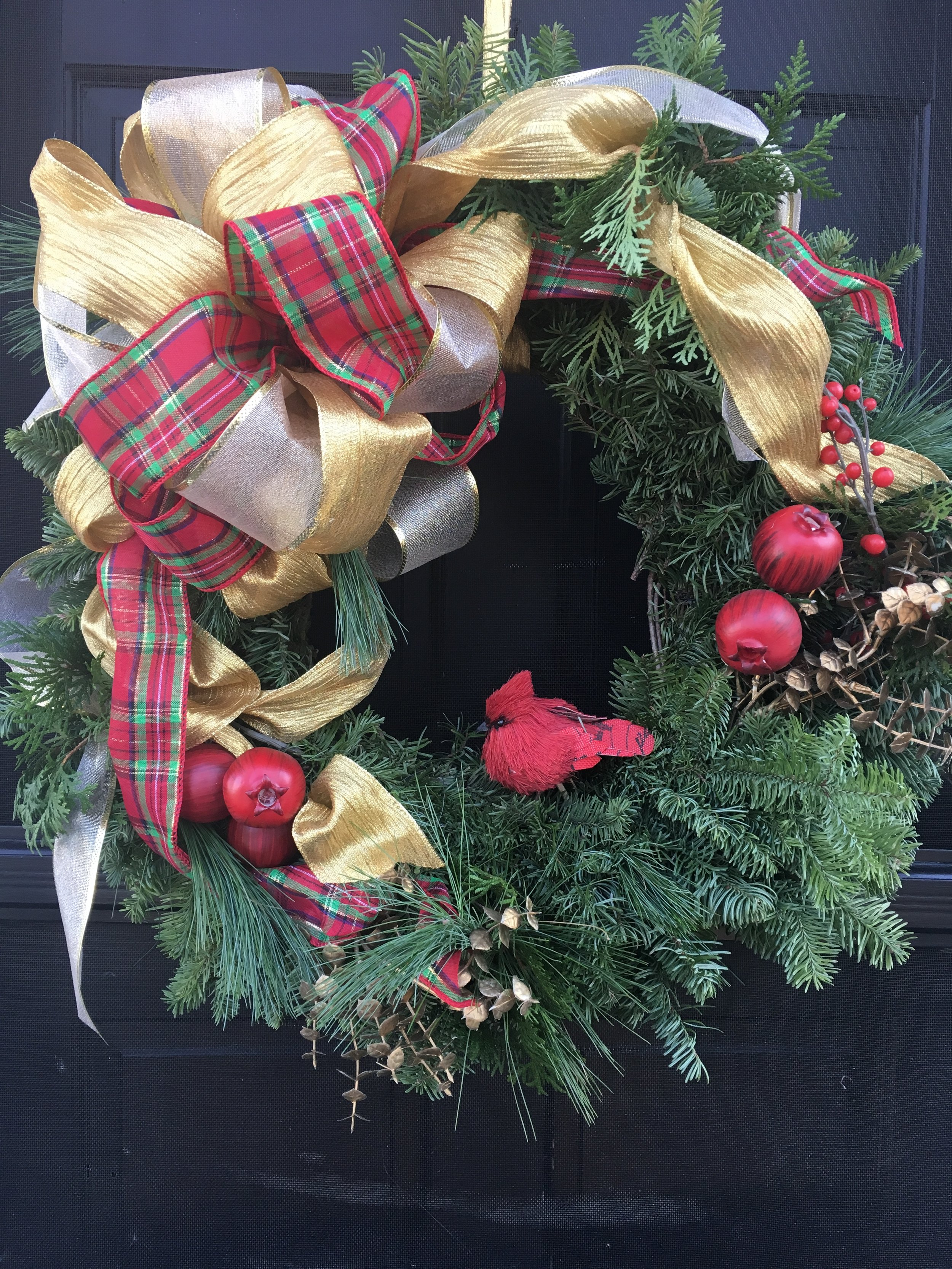 A live exterior door wreath with gold and red accents and plaid and gold ribbons