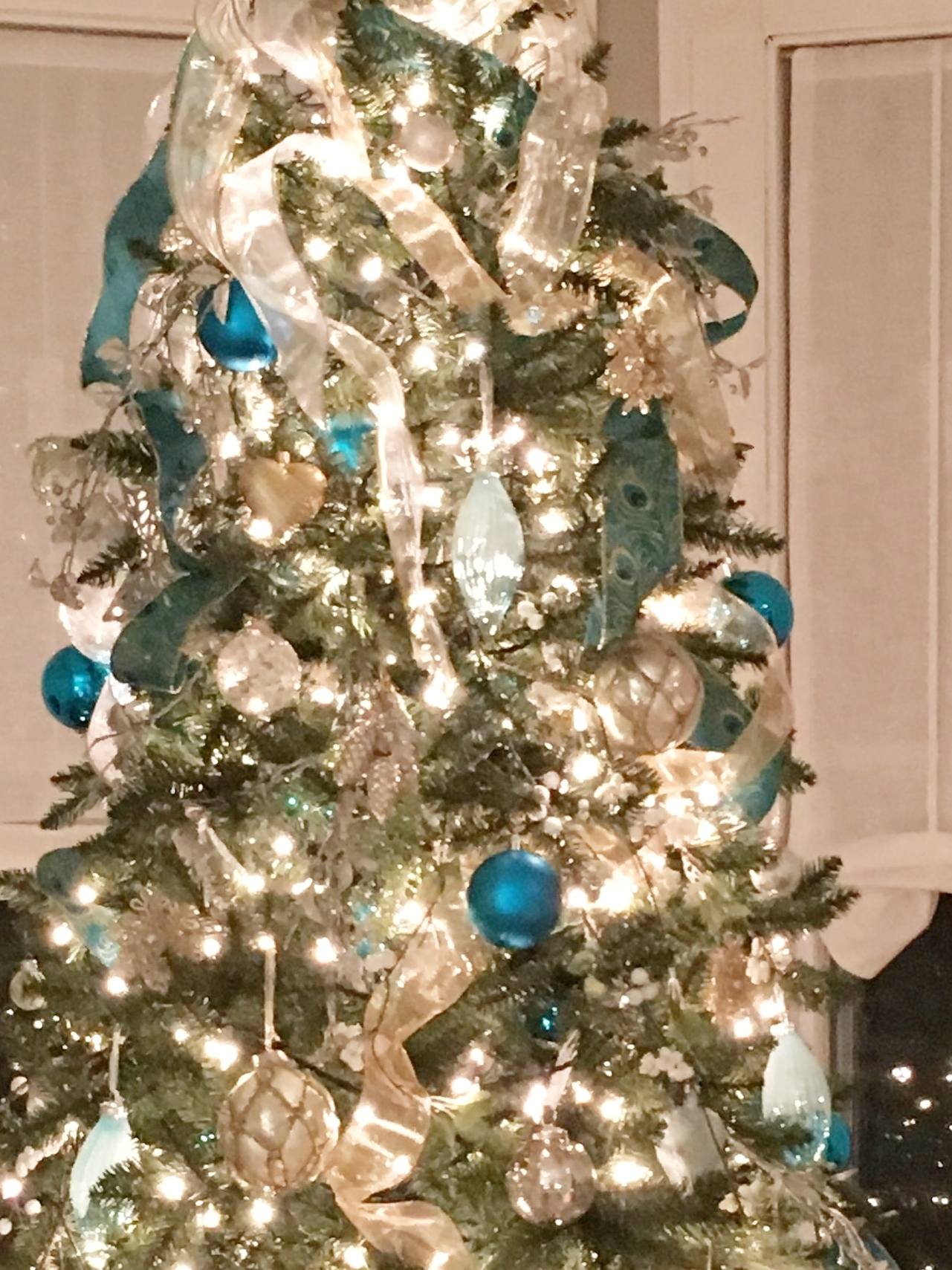 Tree with gold, silver and peacock ribbon embellished with white and silver berry sprigs, aqua teardrop glass ornaments, a mix of matte, sparkly, and shiny teal balls, mercury glass ornaments in a variety of sizes and shapes, and champagne glass pinecone clusters