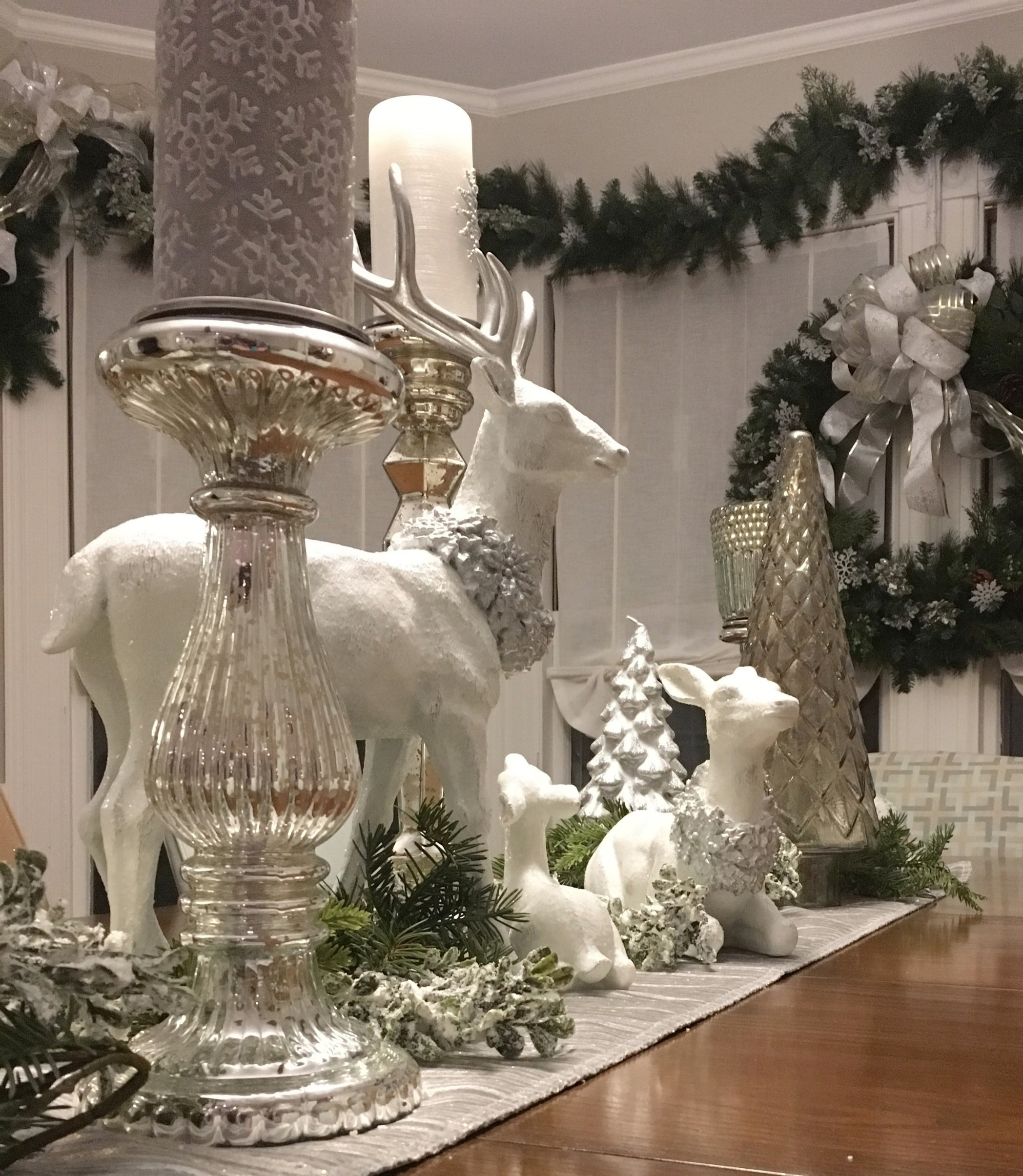 A family of white deer and a collection of mercury glass and candles set amid mixed frosted greens makes a beautiful winter table display