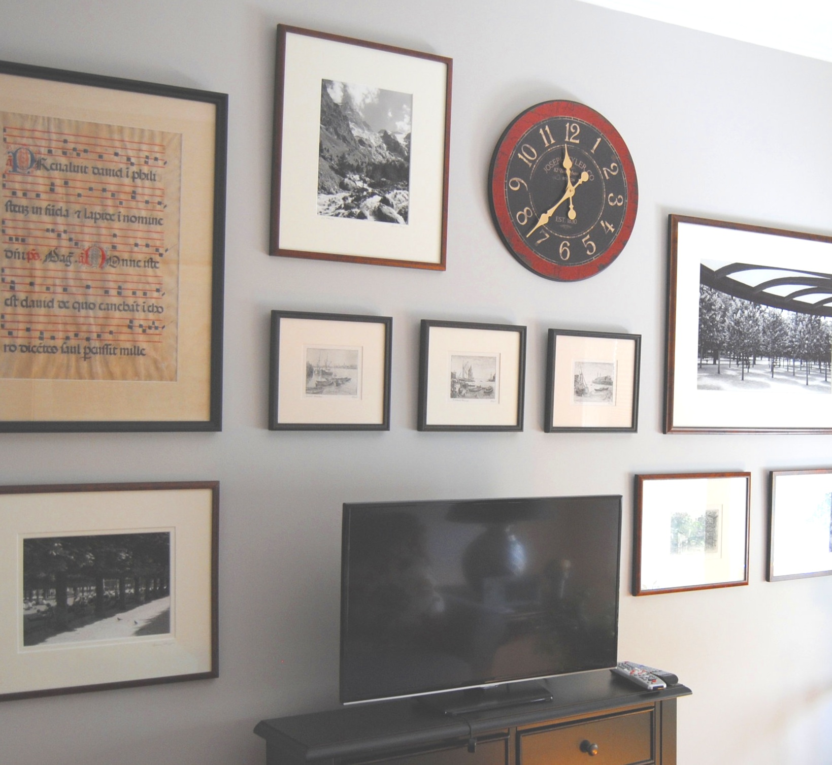 This gallery wall was created with art from the clients' collection and hung to incorporate the TV as part of the design. Touches of black in some of the frames, some of the artwork, and the clock face, as well as the scale of the pieces help to integrate the television seamlessly.