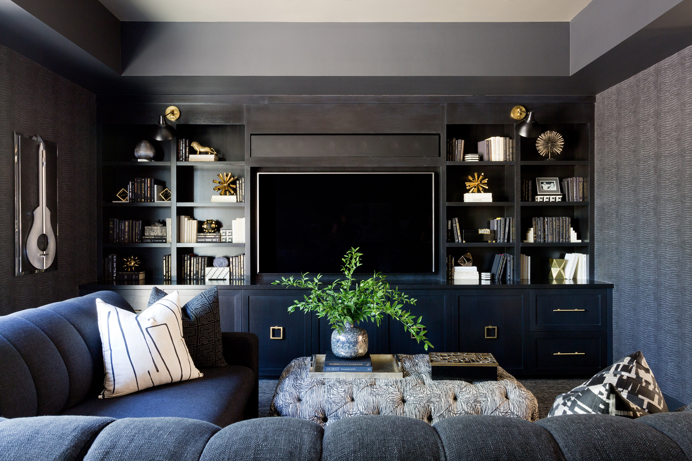 This stunning dramatic media room by   Jenn Feldman Designs   is a beautiful example of painting the wall behind the television a dark color. The bookshelves flanking the television are expertly styled in a limited contrasting color palette with creams and golds adding interest and warmth to the design.