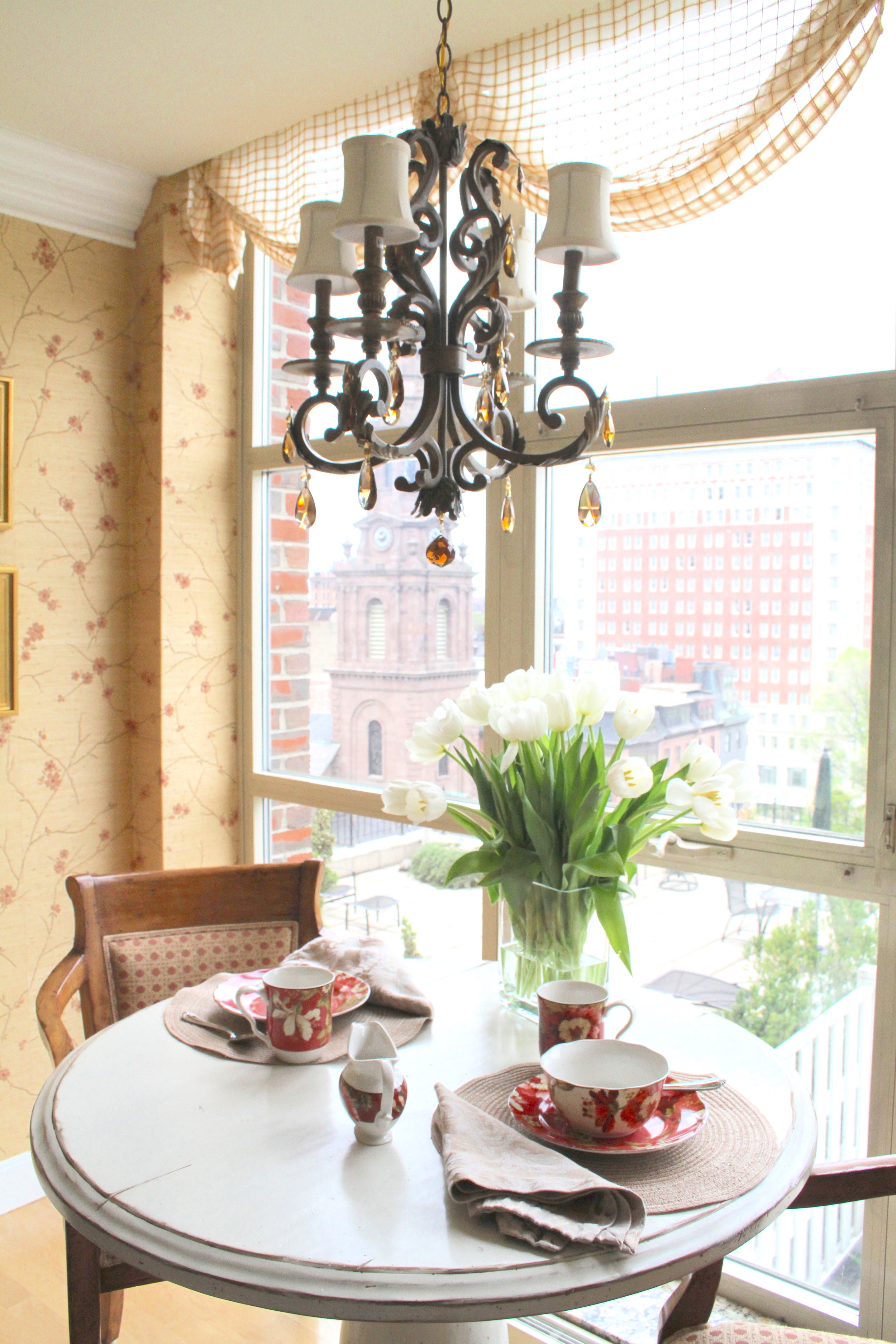This petite chandelier is just the right scale in this condo breakfast nook over a small table for two overlooking the city.