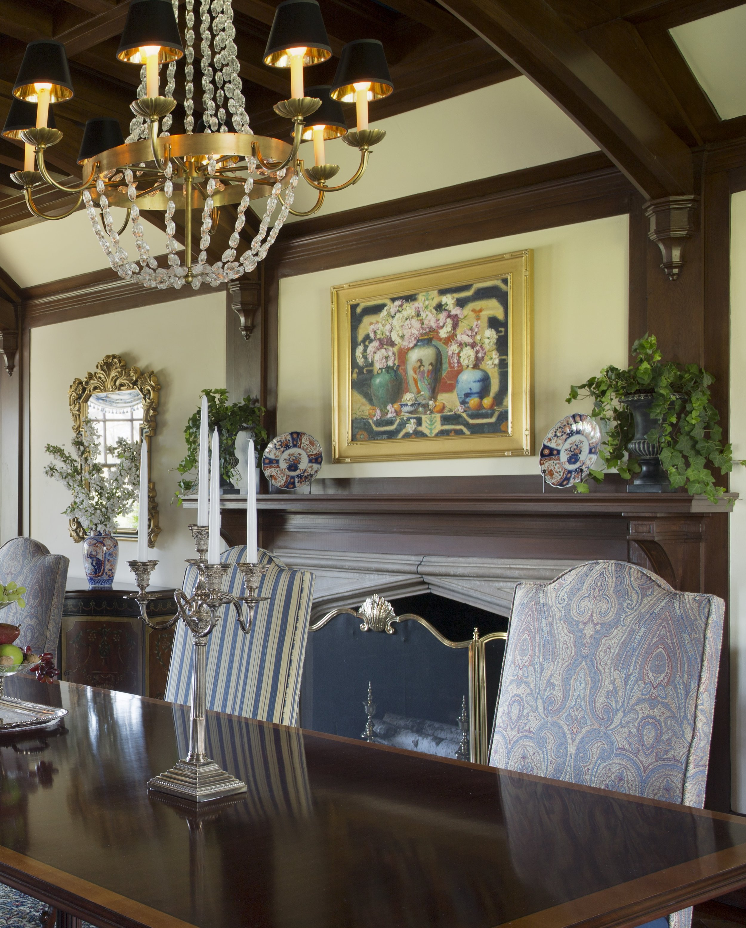 This symmetrical mantel arrangement works in this very formal dining room. The symmetry continues along the wall with matching pairs of painted cabinets topped with floral arrangements in front of gilded mirrors on either side of the fireplace. The dining table holds another symmetrical arrangement with an antique silver epergne flanked by candelabra.