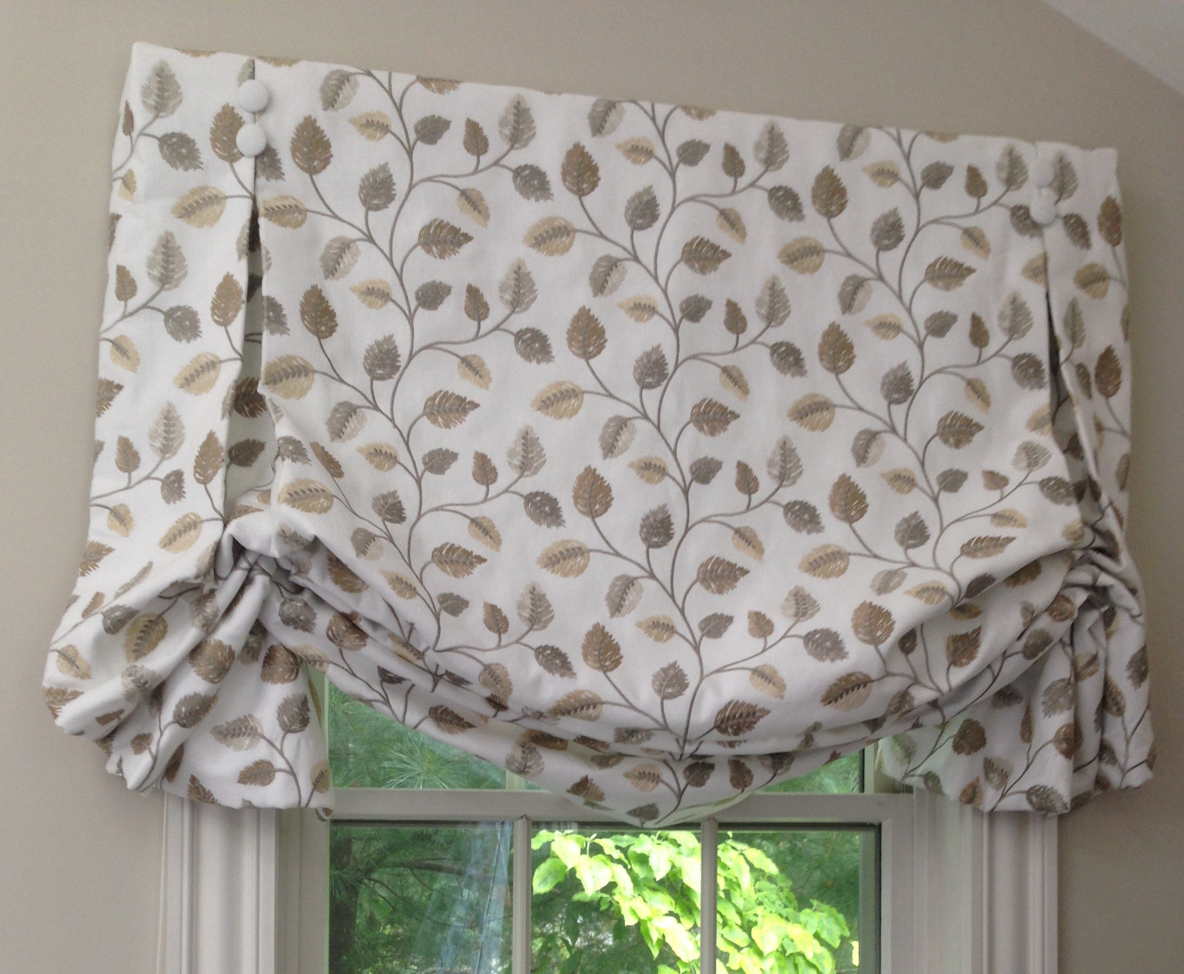 This outside mount, lined and interlined, custom soft Roman shade has fabric that wraps around the ends of the board to the wall. Inverted pleats held at the top by covered buttons were added for a softer, fuller profile.