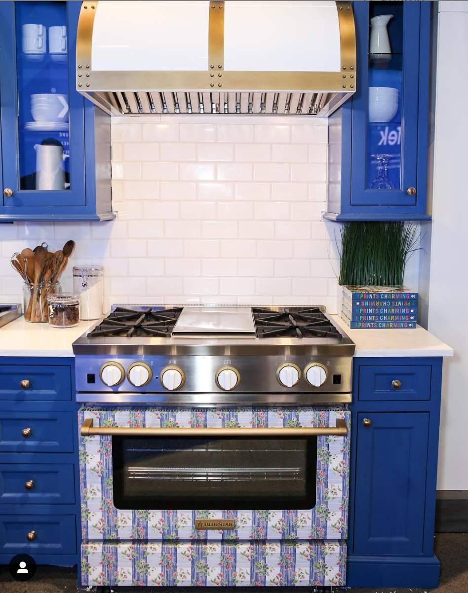 Bright blue cabinets surround a   Bluestar range   in a print by Madcap Cottage at   KBIS