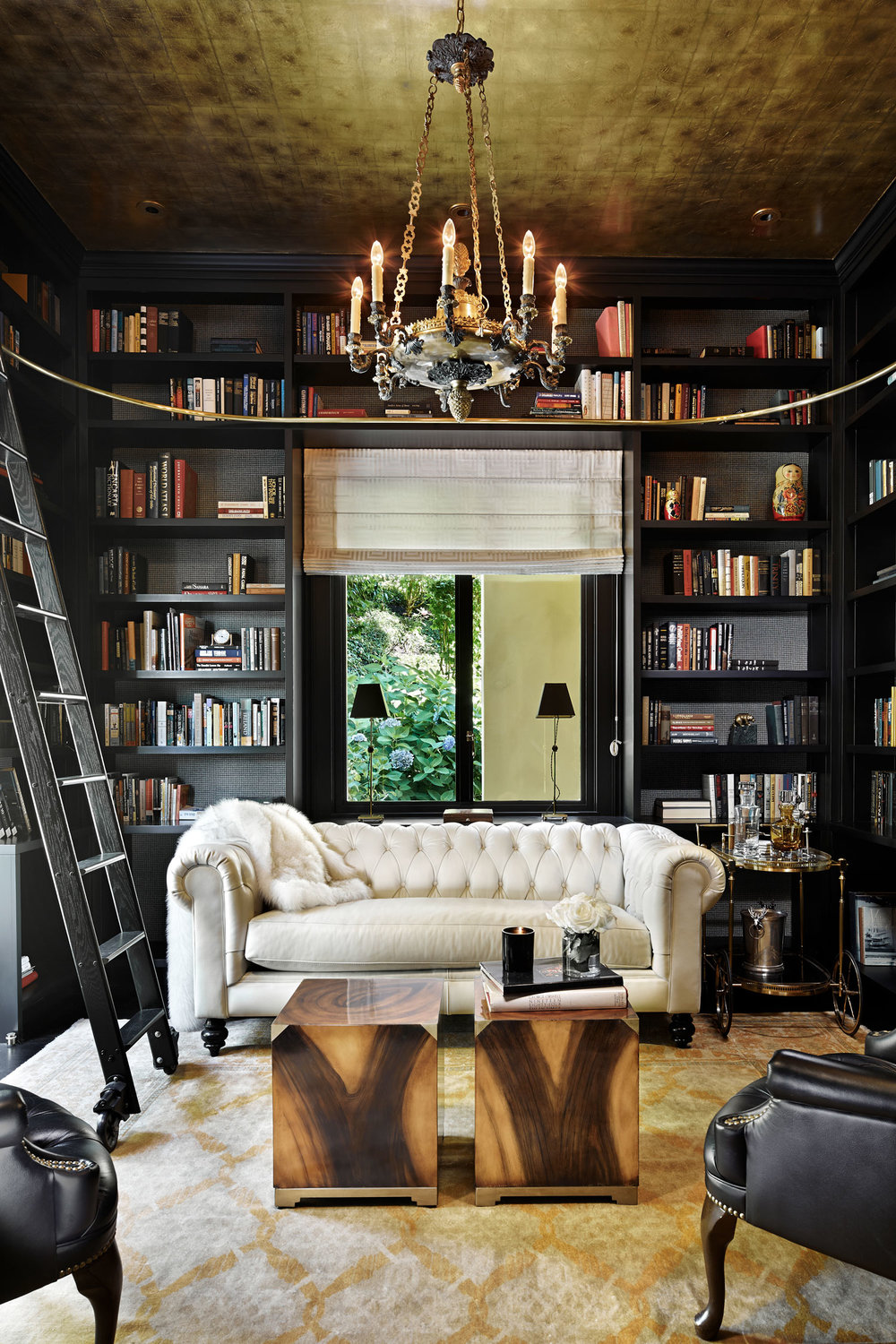Black walls of bookshelves are paired with a gold ceiling in this library by   NB Design Group  . Photographer:   Benjamin Benschneider