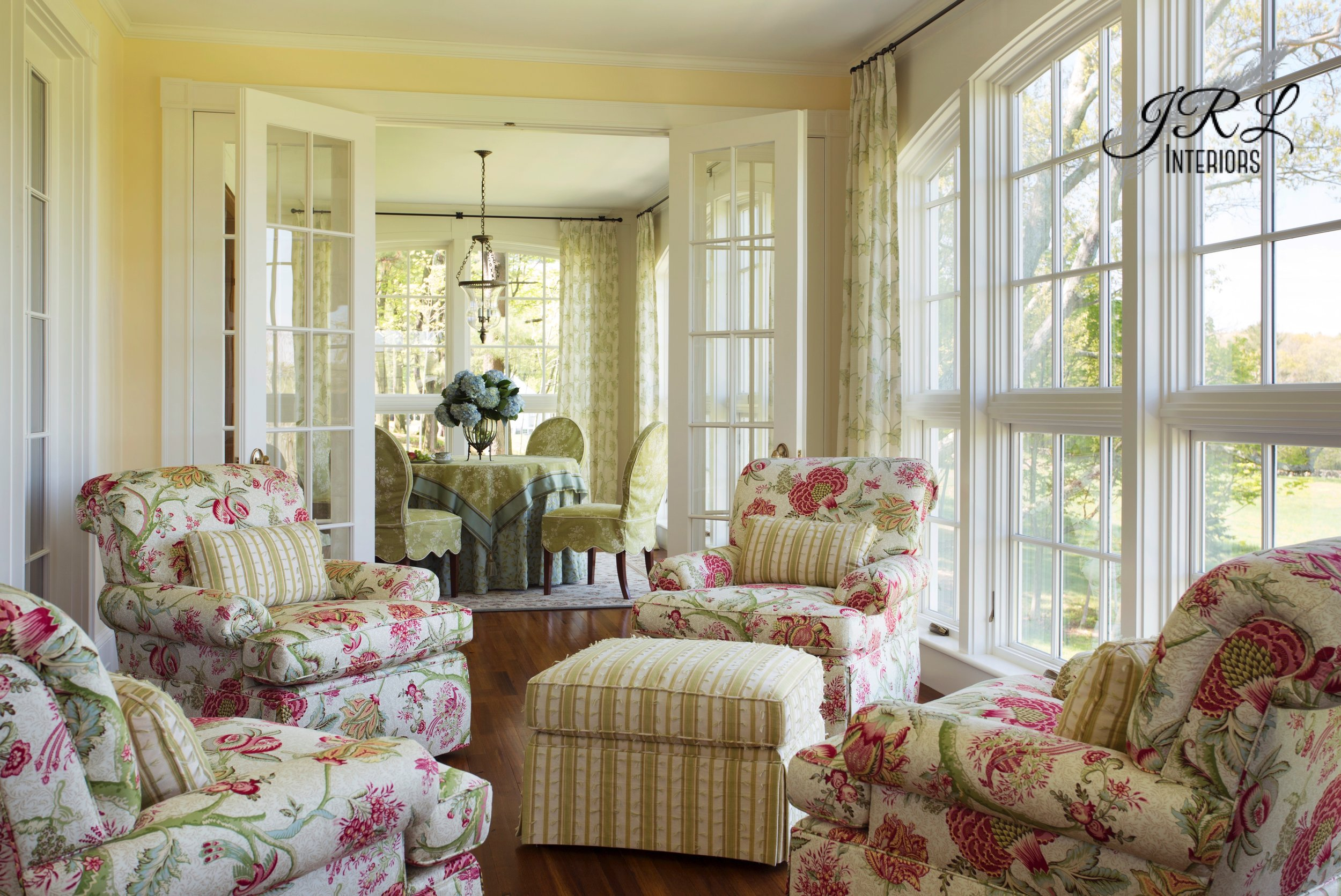 These sunny yellow walls and crisp white millwork provided a cheery backdrop for the riot of fresh spring colors in this sunroom space we designed several years ago.