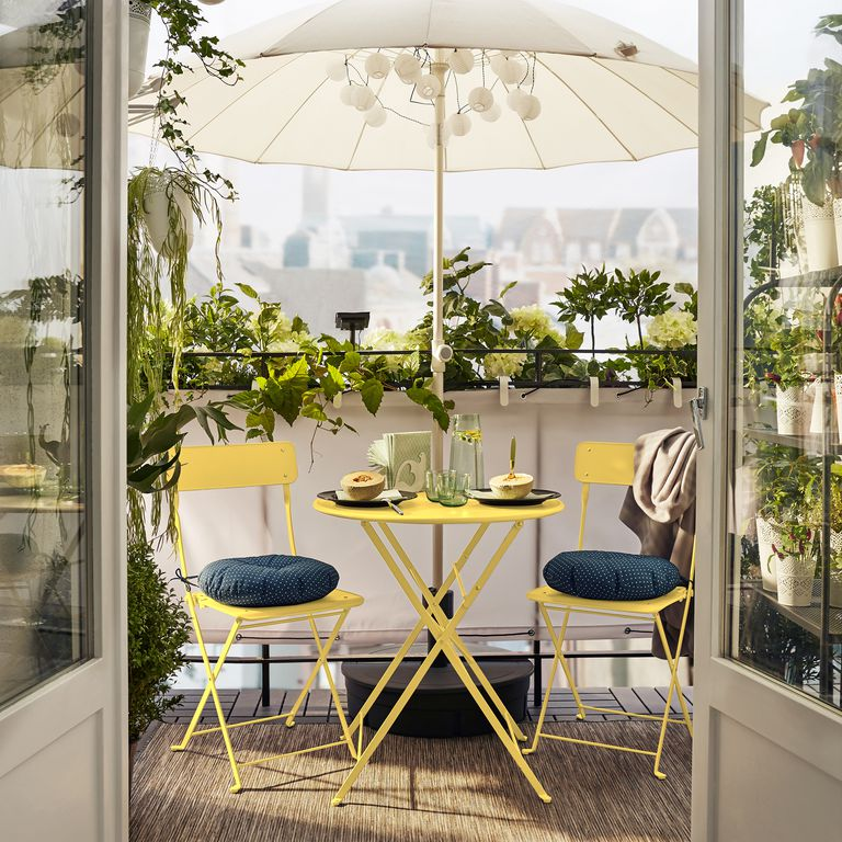 A pocket garden on a balcony with a yellow cafe set. Image via   House Beautiful.     Photo by Martin Inger for IKEA