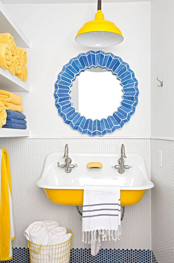 Perky yellow accents add a jolt of energy to this blue and white bath. Image via   Country Living   ,  photo by   Buff Strickland