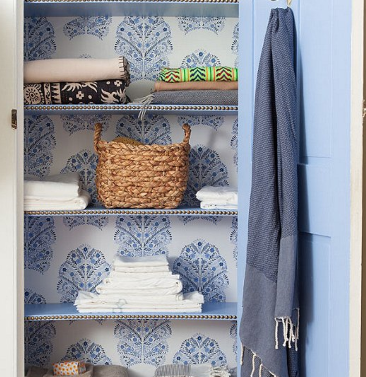 Wallpapered linen closet with embellished shelves at   One Kings Lane