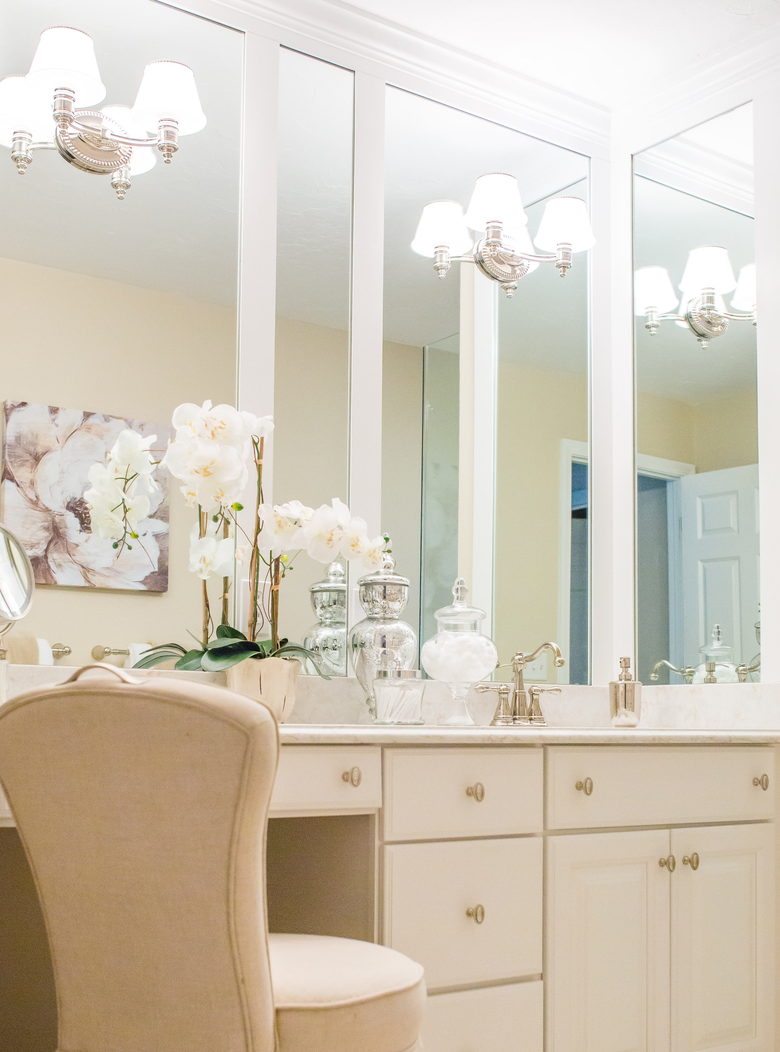 We always design bathroom mirror trim to line up with and complement the cabinetry below. Trim and mirror wrap all three sides of this vanity alcove, and light fixtures were mounted through the mirror to effectively increase the light produced.