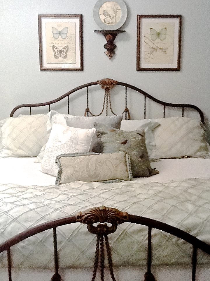 A curved headboard topped with a group of artwork