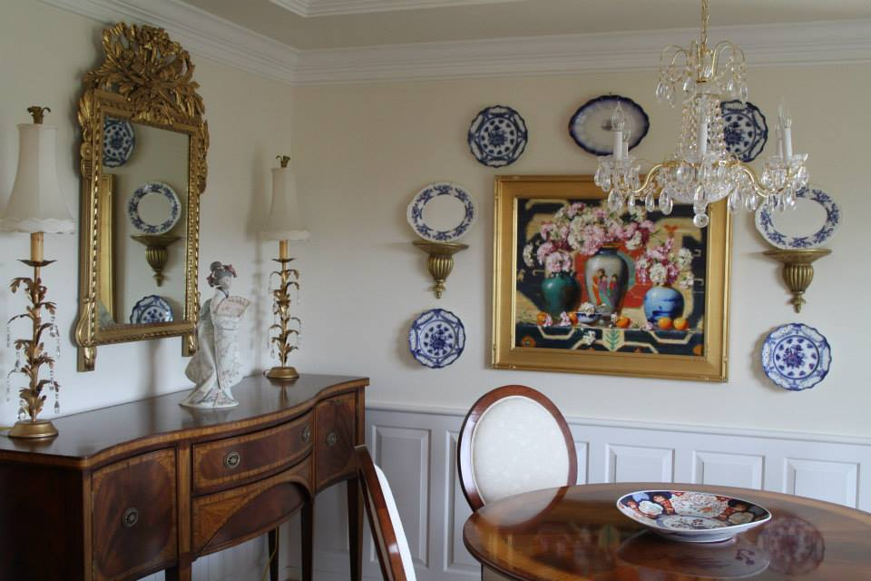 A mix of artwork, plates and a mirror on the walls of this dining room