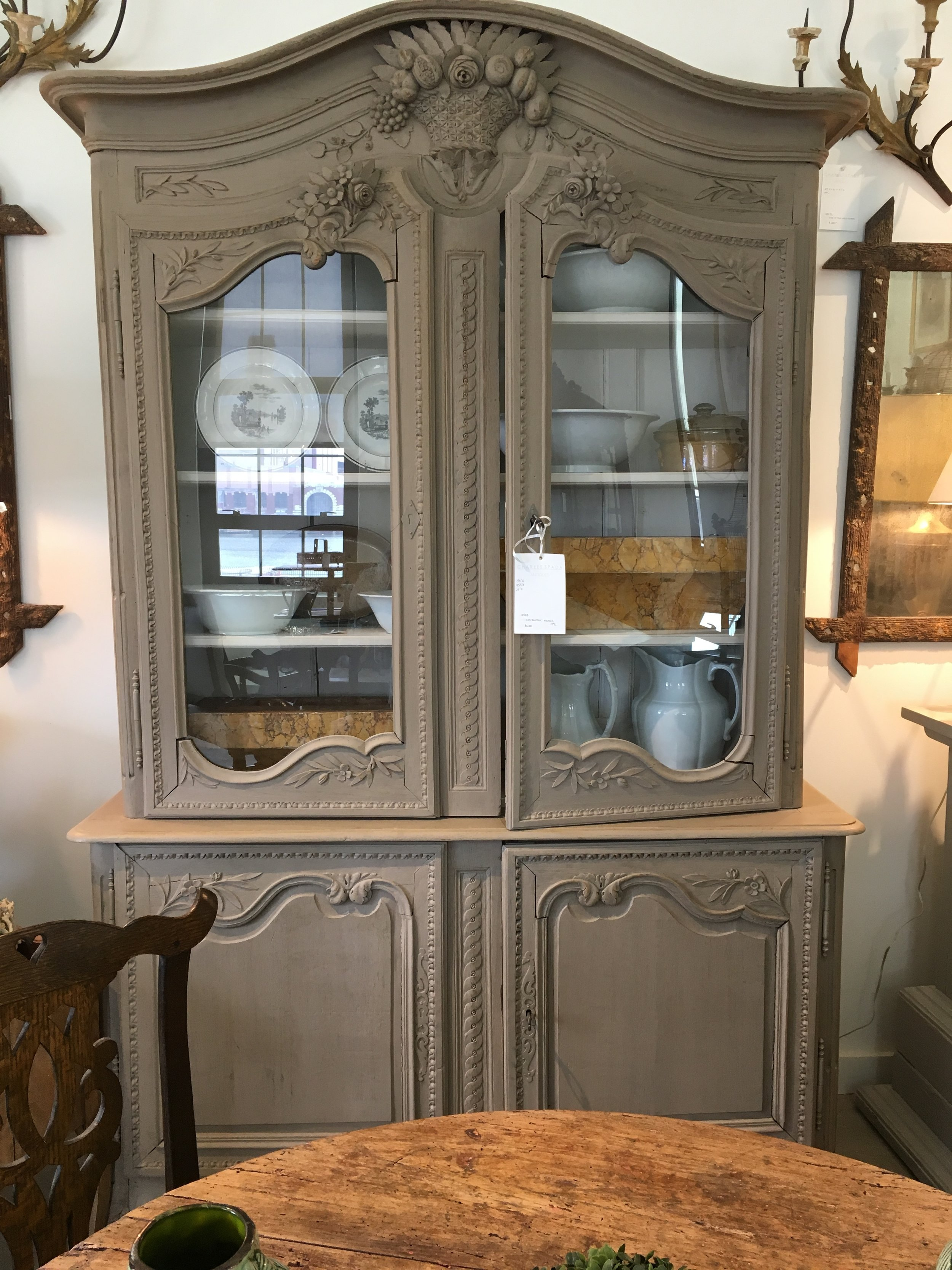 The taupe painted finish on this pretty French oak glass doored cabinet really lightens and tones down the formality on this piece.
