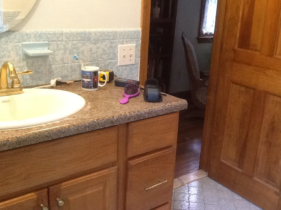 Honey oak cabinetry, brass faucets, and barf-patterned laminate counters on the vanity. More blue tile on the floor…same color and texture as the walls, different shape - not sure that's an improvement….