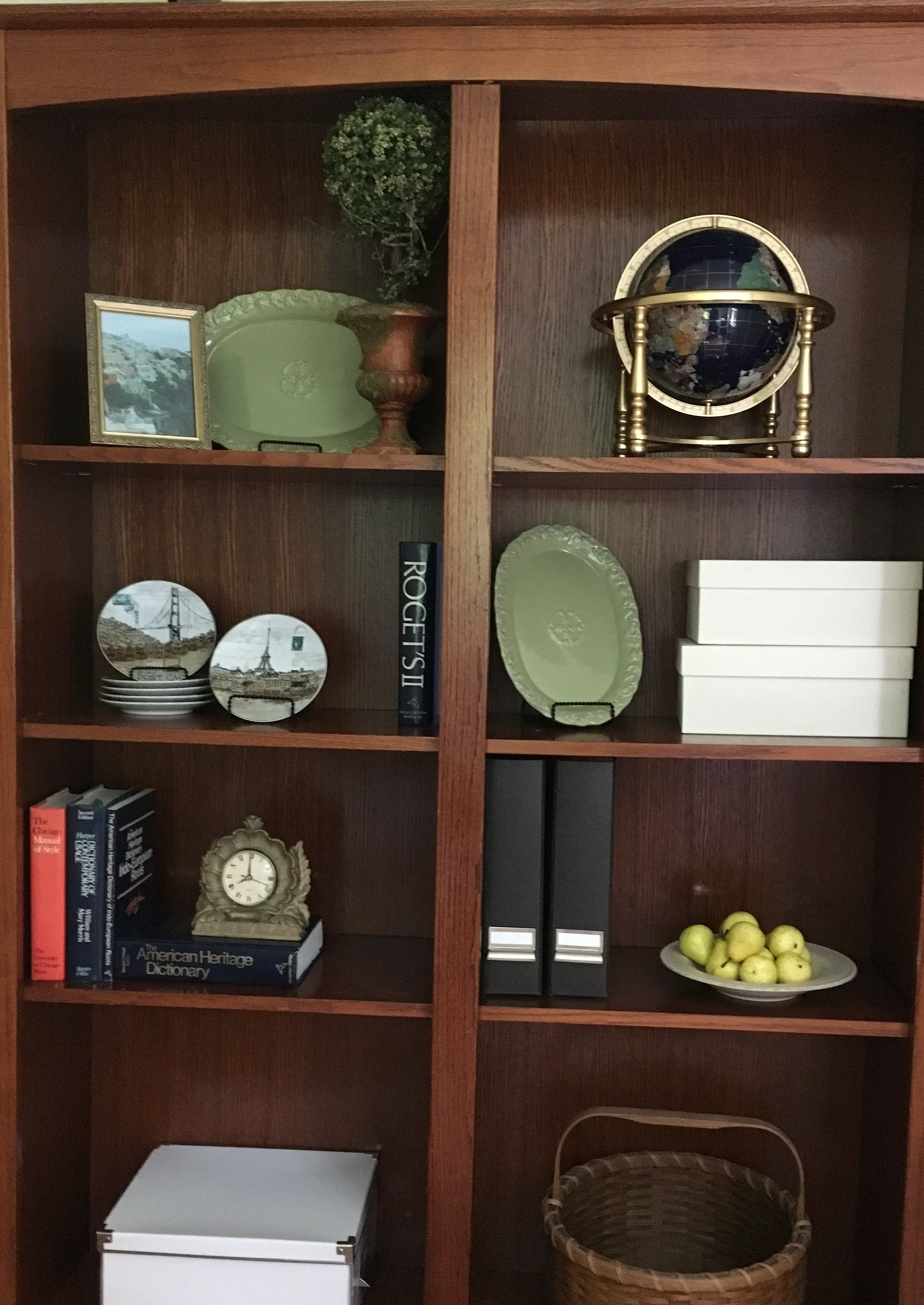 The office bookcase continues our aspirational travel theme with a globe, and pictures and scenes from far away places. Any necessary clutter is contained in magazine files and decorative boxes.