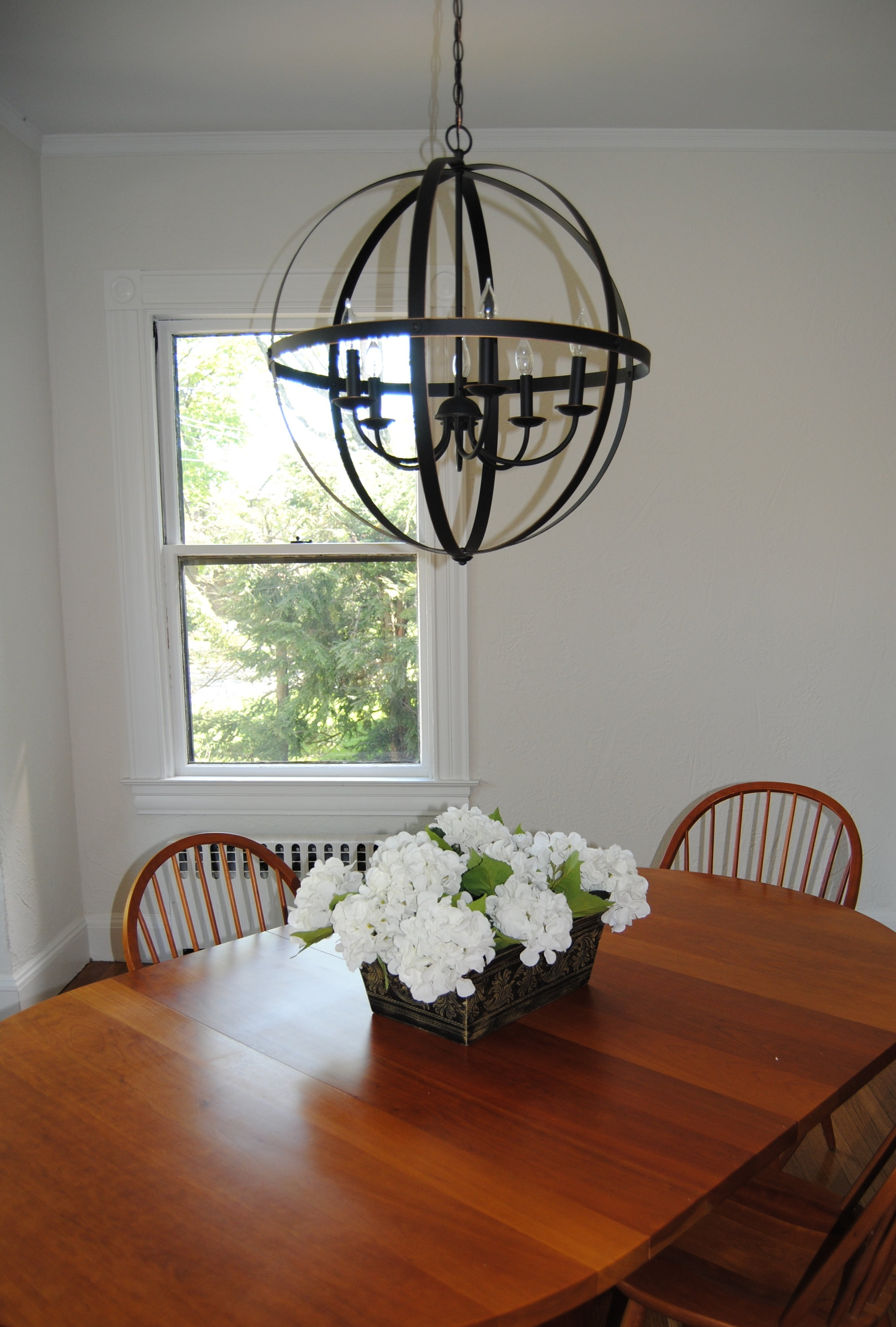 Updating the light fixture from a homely ceiling mount to this orb chandelier made a spectacular difference in the mood of this dining room in this gracious antique Victorian with 9 ft ceilings!