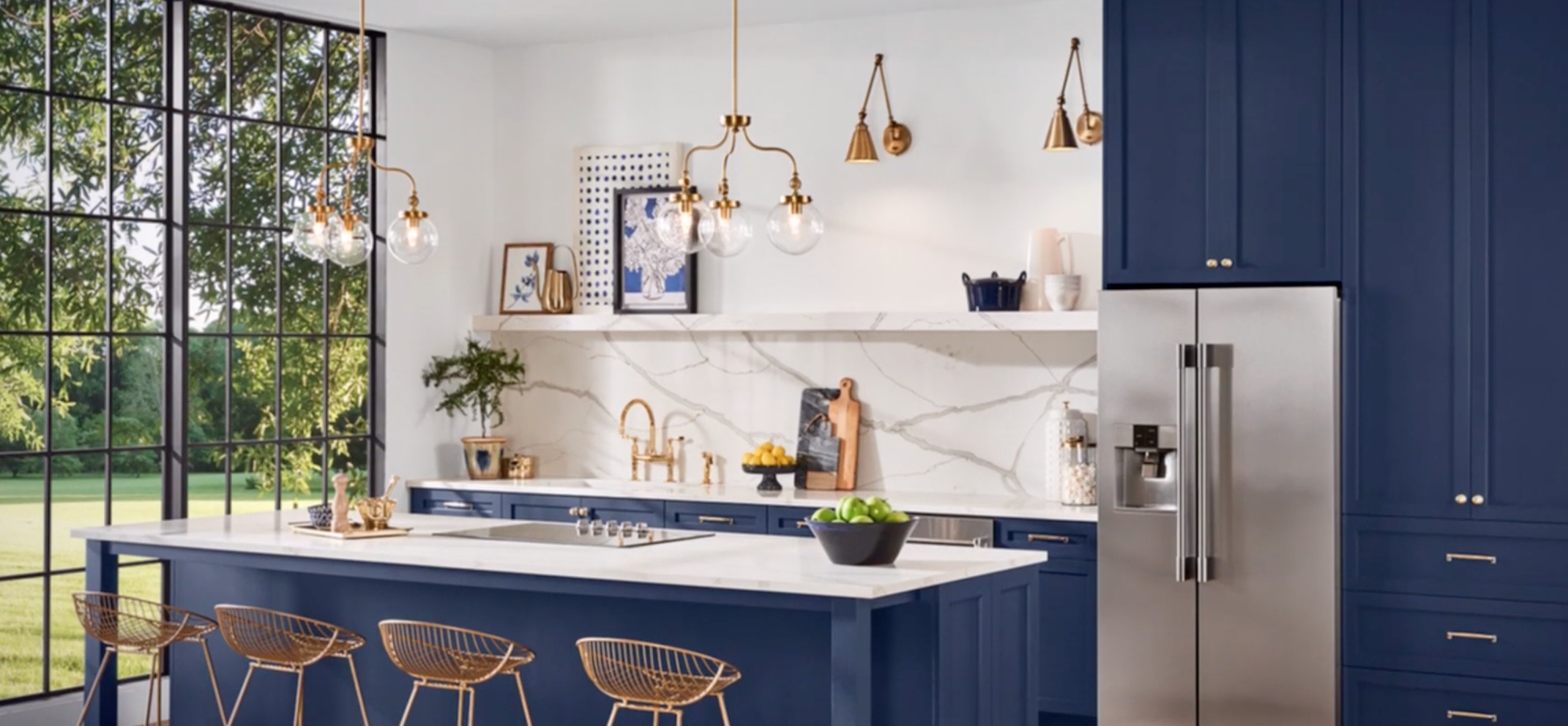 Here, Sherwin Williams Naval is paired with white marble and natural brass accents alongside stainless steel appliances and hardware. The look is both rich and classic. Image via   Sherwin WIlliams