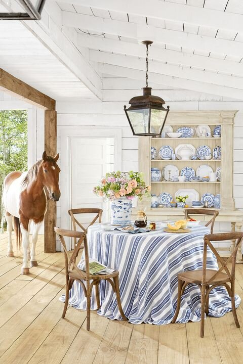Authentic Farmhouse (note the actual farm animal) featuring simple lanterns, an abundance of white painted shiplap, rustic simple furnishings, and classic blue and white. Photo by   Brian Woodcock,   Styling by   Page Mullins  . Photo via   Country Living