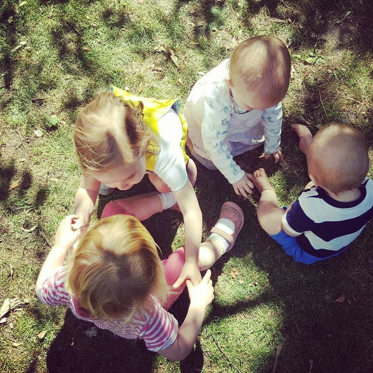Four children play together on grass