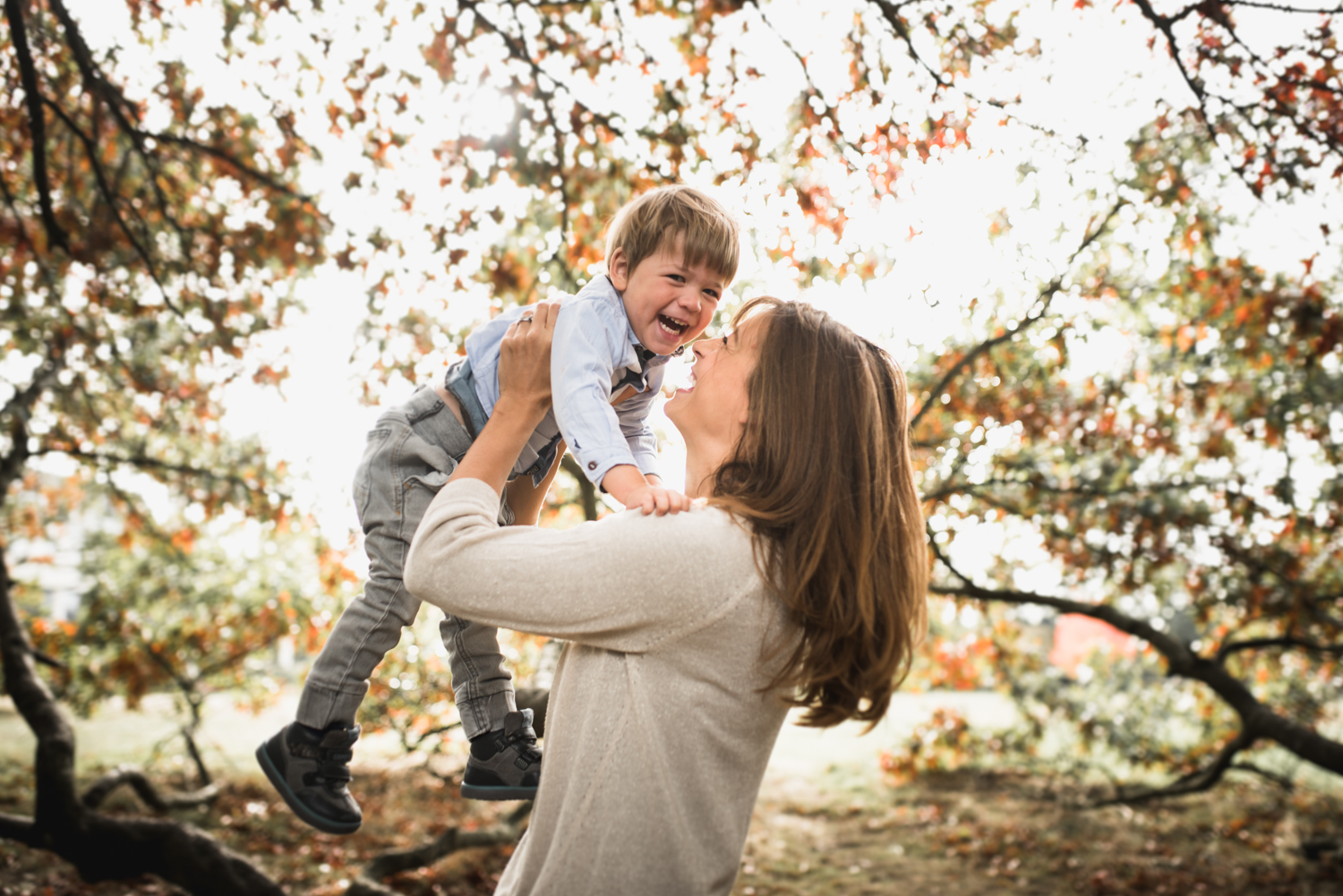 Mother lifts son in air by Hampshire Family Photographer Evie Winter